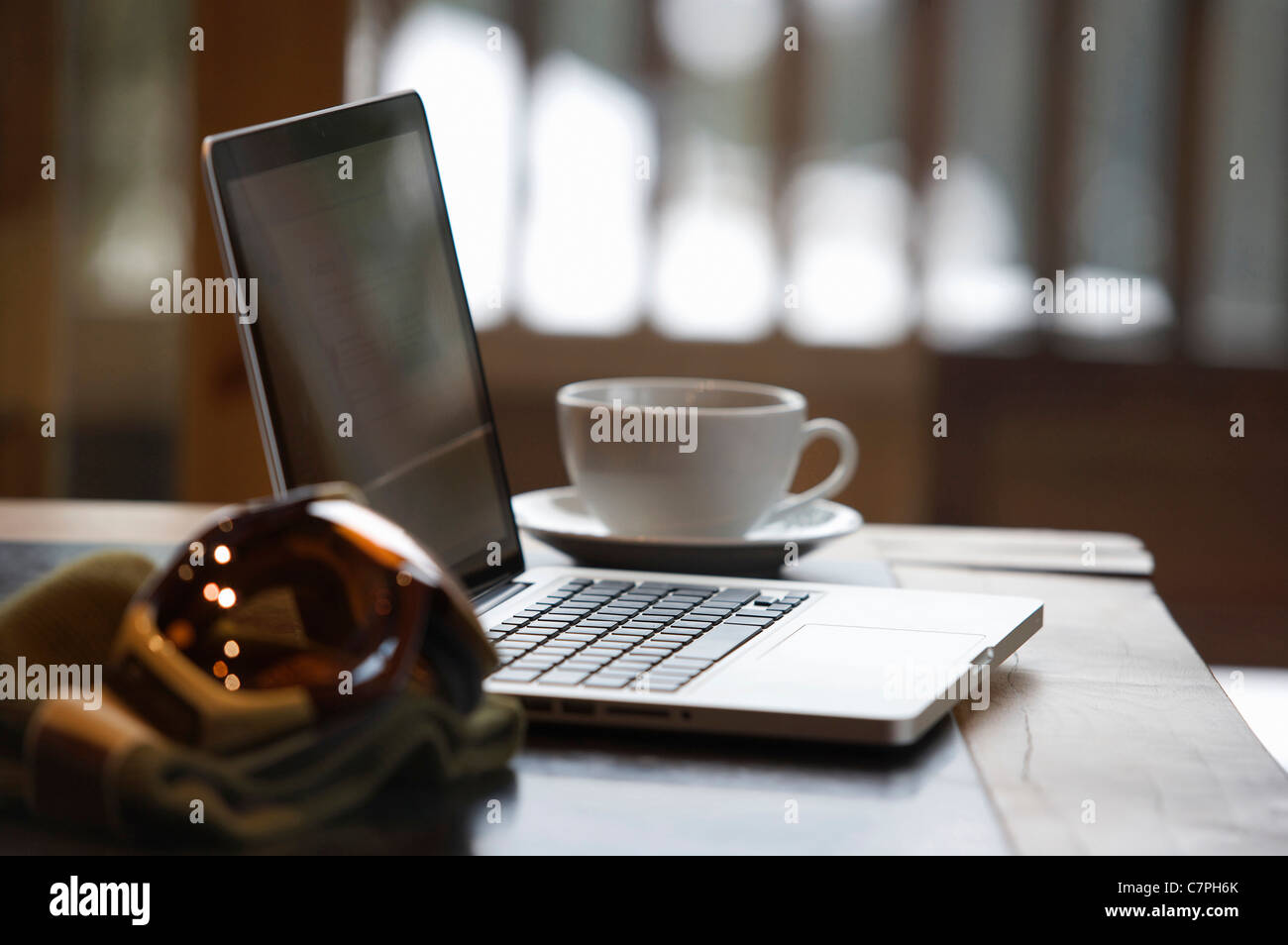 Ski goggles and laptop with coffee cup - Stock Image