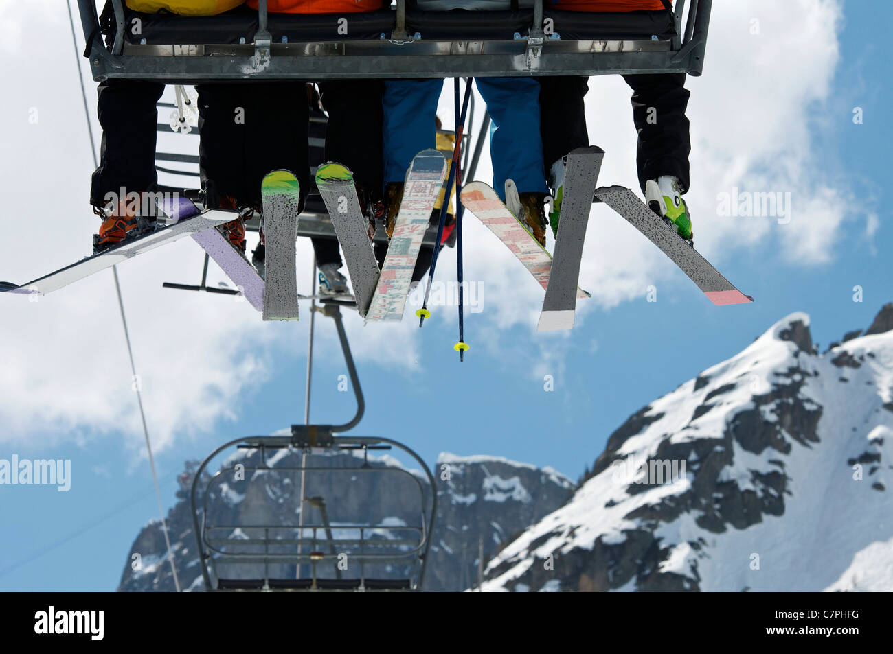 Skiers riding chair lift over mountains - Stock Image