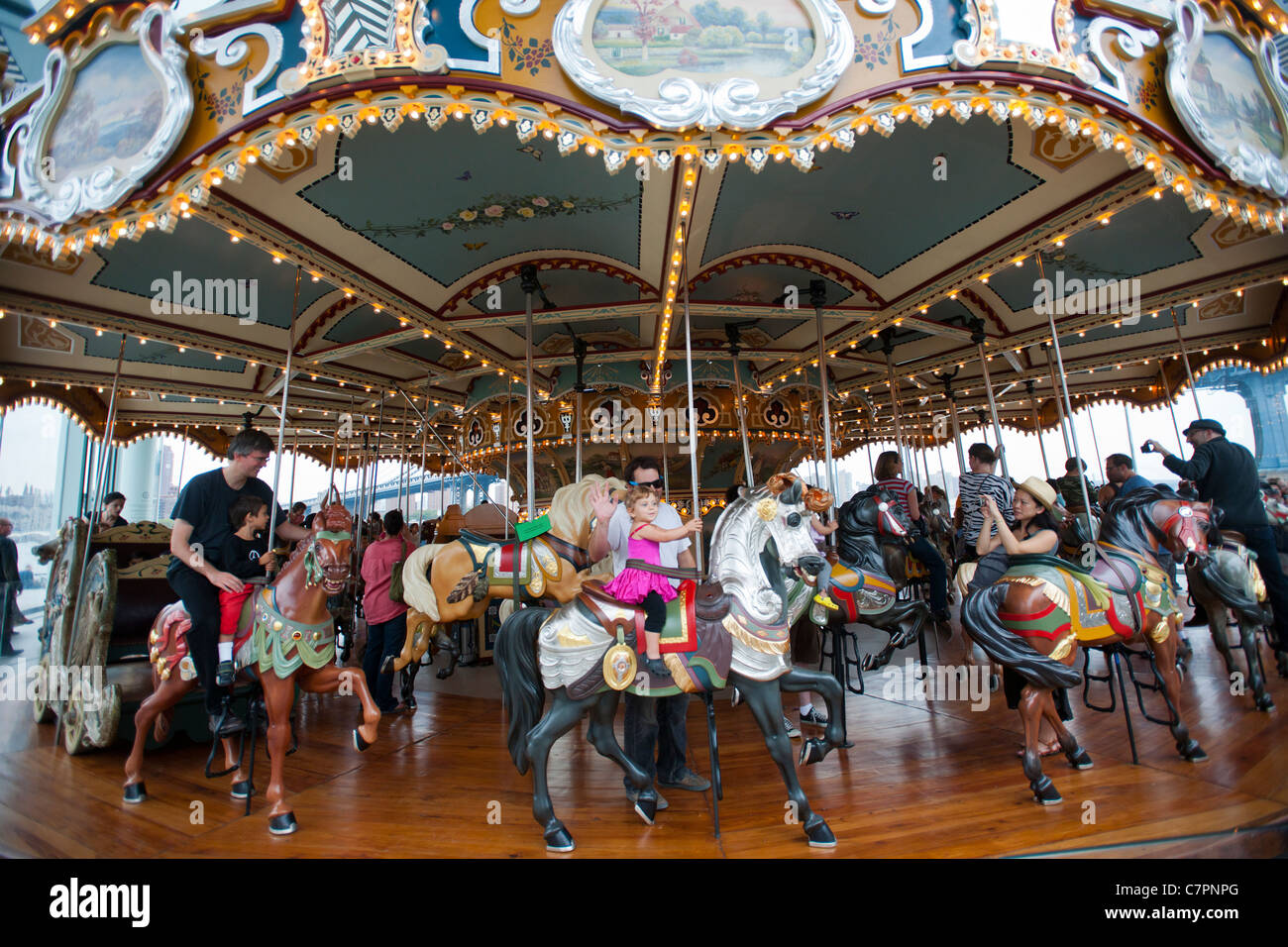Visitors to Brooklyn Bridge Park enjoy the newly opened and restored Jane's Carousel - Stock Image
