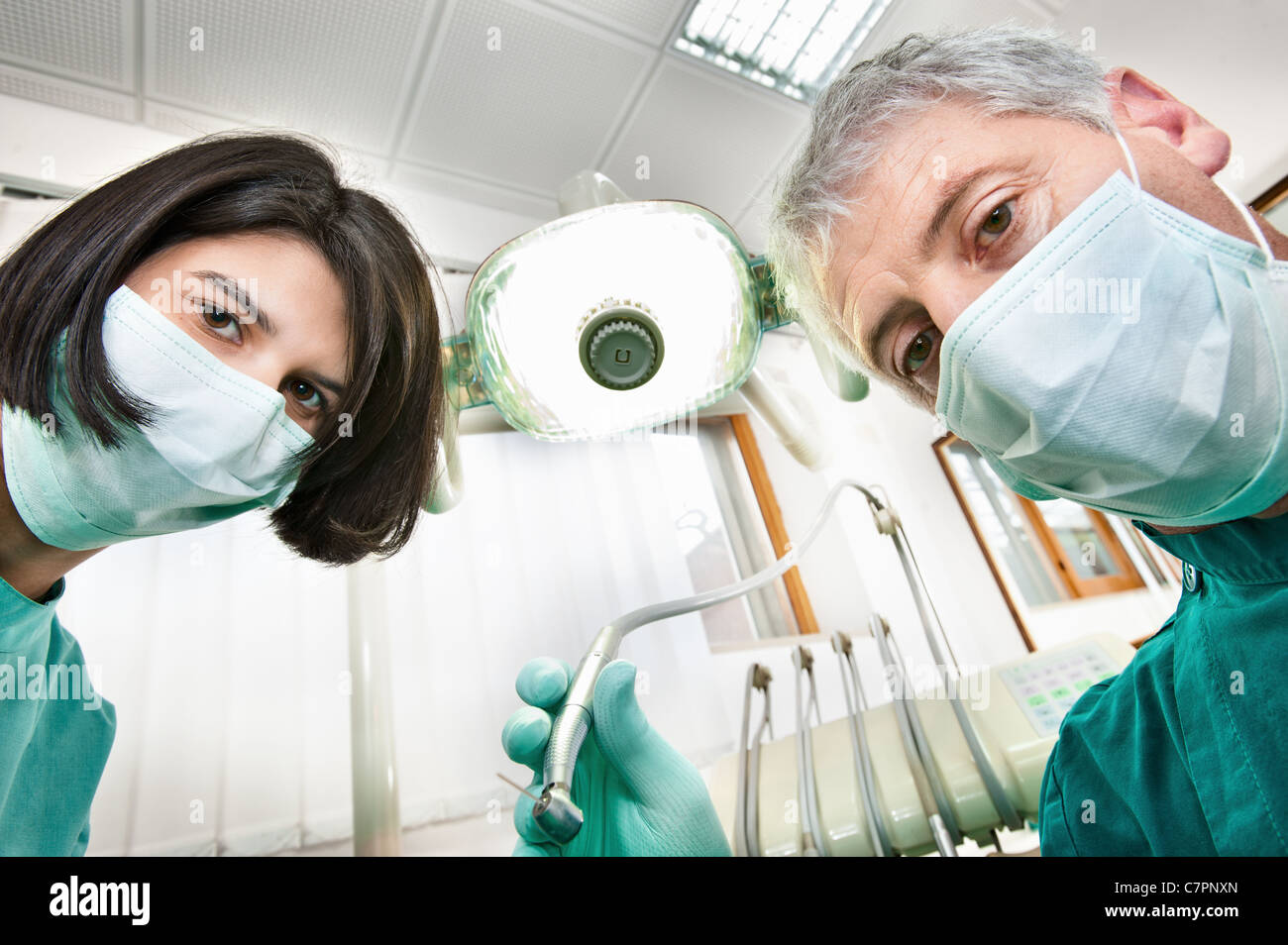 Dentist and assistant working in office - Stock Image