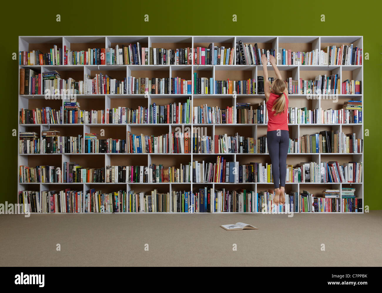 Girl jumping for book on high shelf - Stock Image