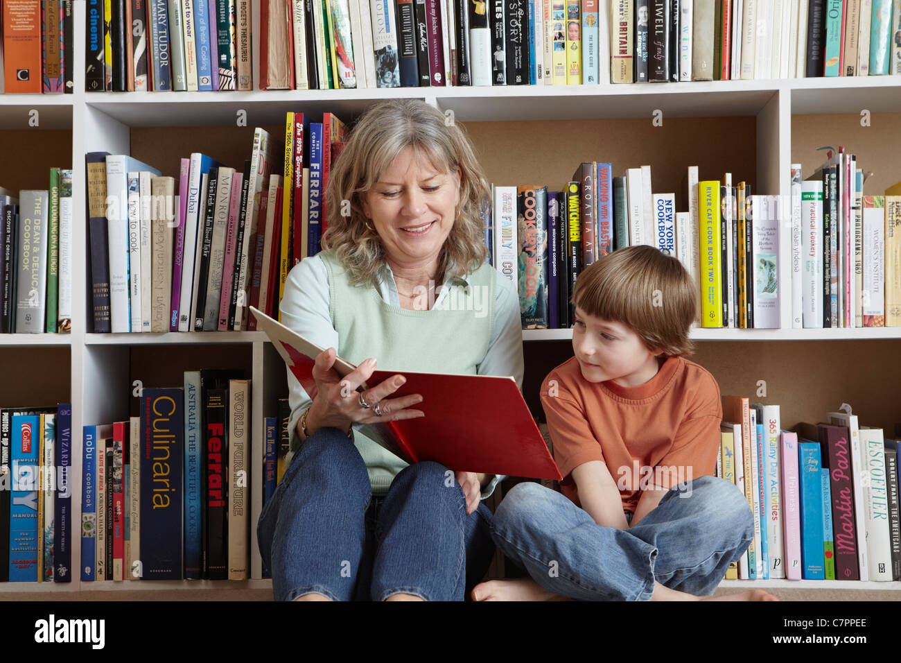 Woman reading with grandson by bookshelf - Stock Image