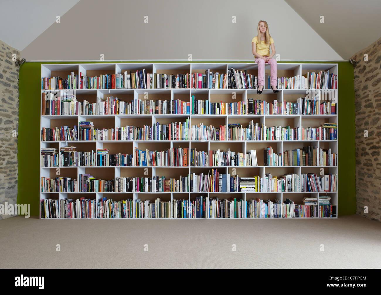 Girl sitting on top of bookshelves - Stock Image