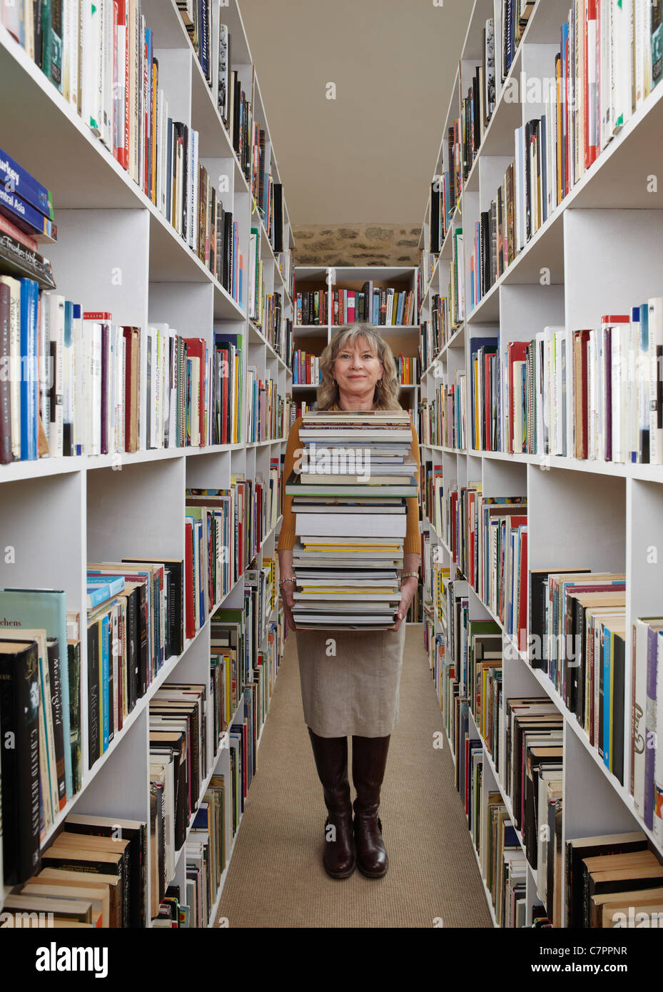 Older woman carrying books in library - Stock Image