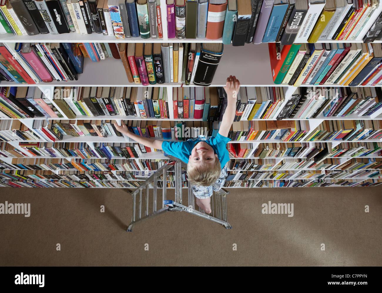 Boy using stepladder on bookshelves Stock Photo