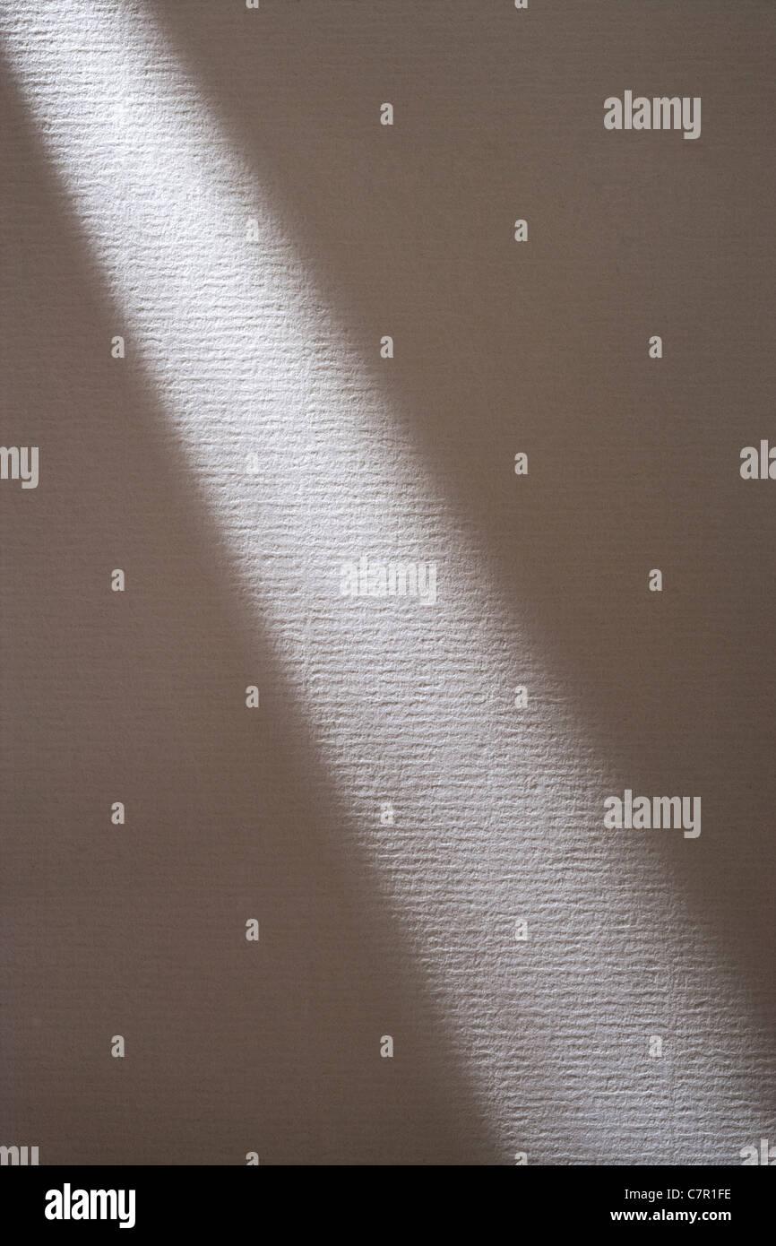 Shaft of light across white textured paper. - Stock Image