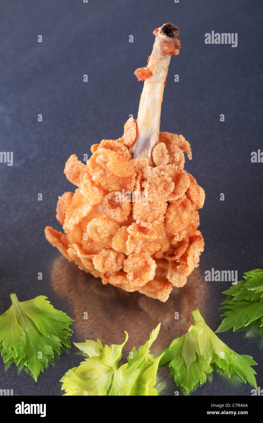 Chicken drumstick coated with corn flakes - closeup - Stock Image