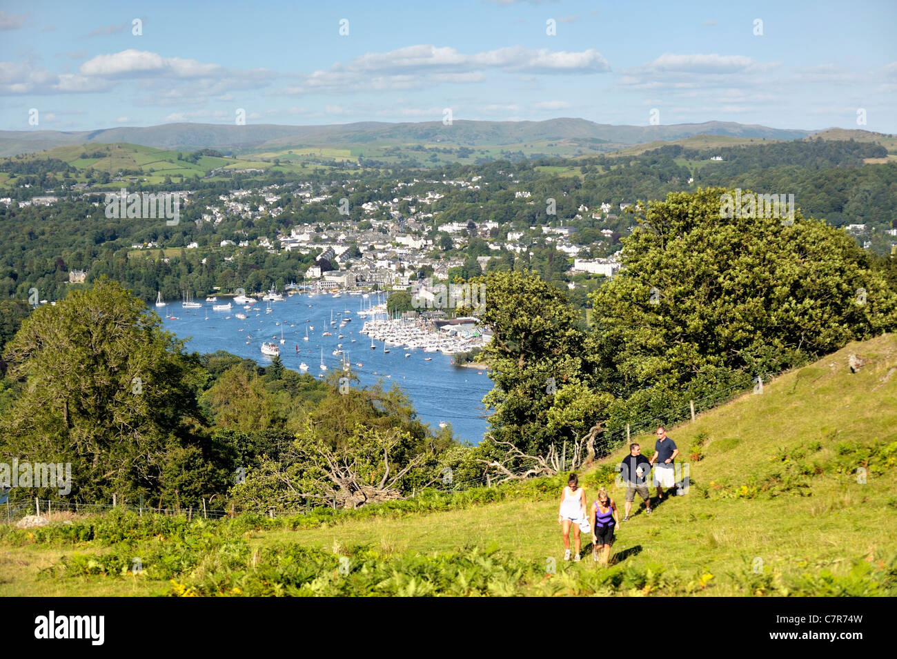 Walkers above Windermere. Lake District National Park, Cumbria, England. N.E. over Bowness on Windermere from above - Stock Image