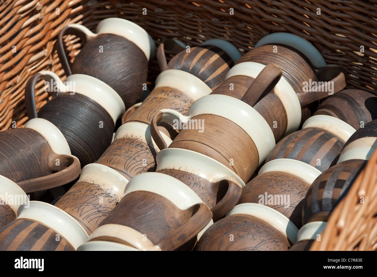 handmade pottery products in a basket sold at traditional urban market - Stock Image