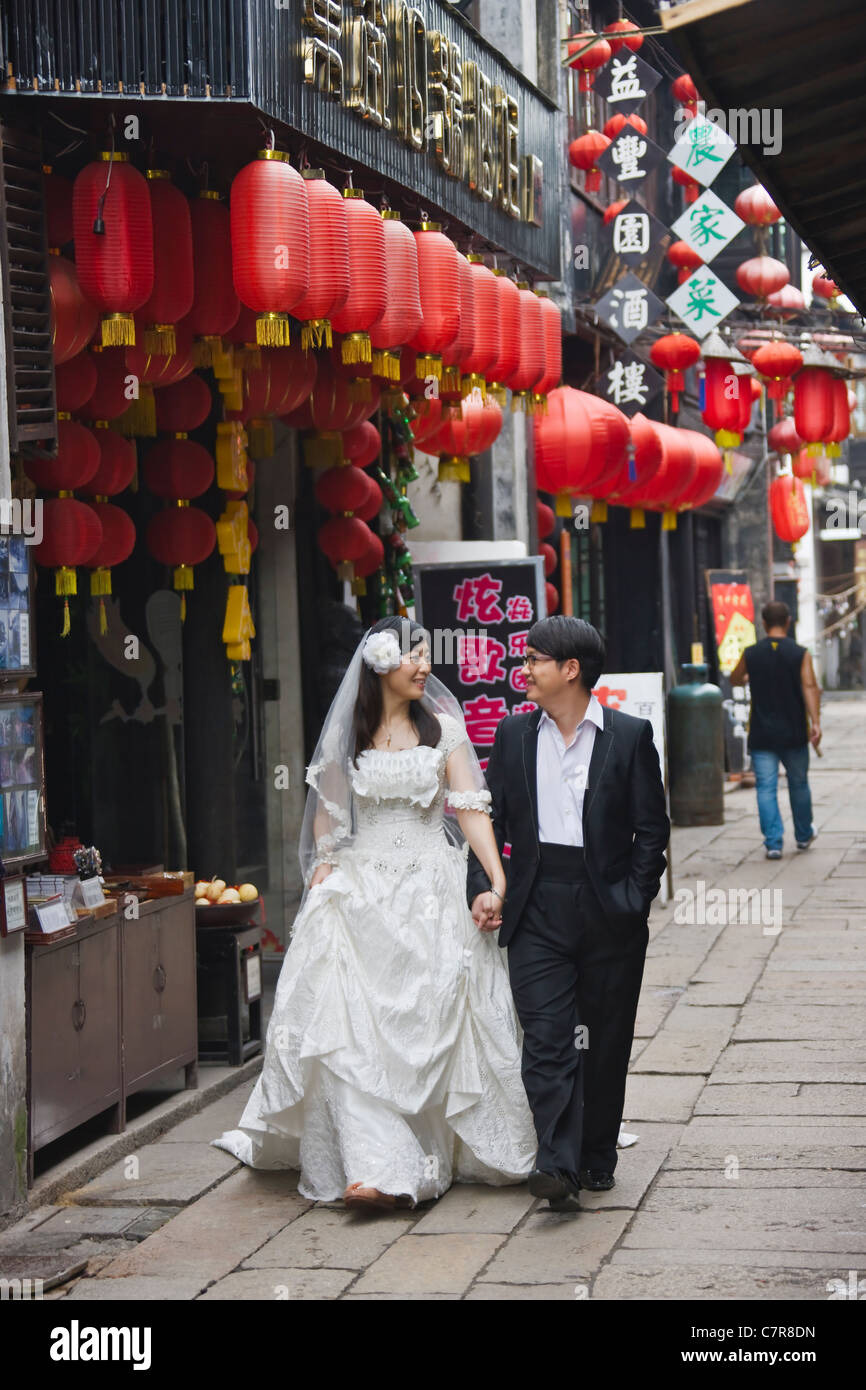 Newly wed in wedding gown strolling on cobbled street with old residence, Xitang, Zhejiang Province, China - Stock Image