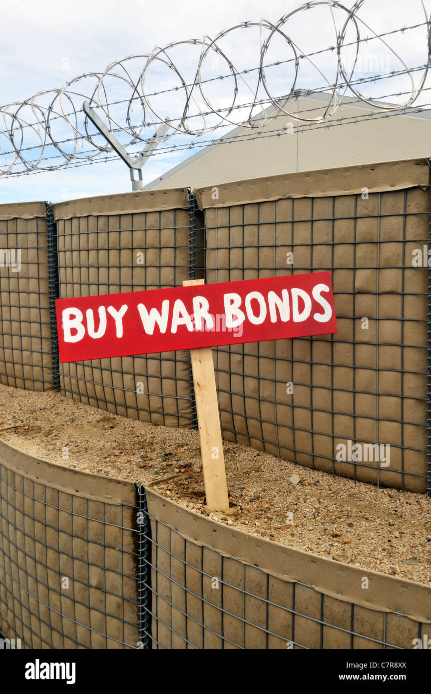 Nostalgic Buy War Bonds sign posted in a barricade with barb wire fence. USA - Stock Image
