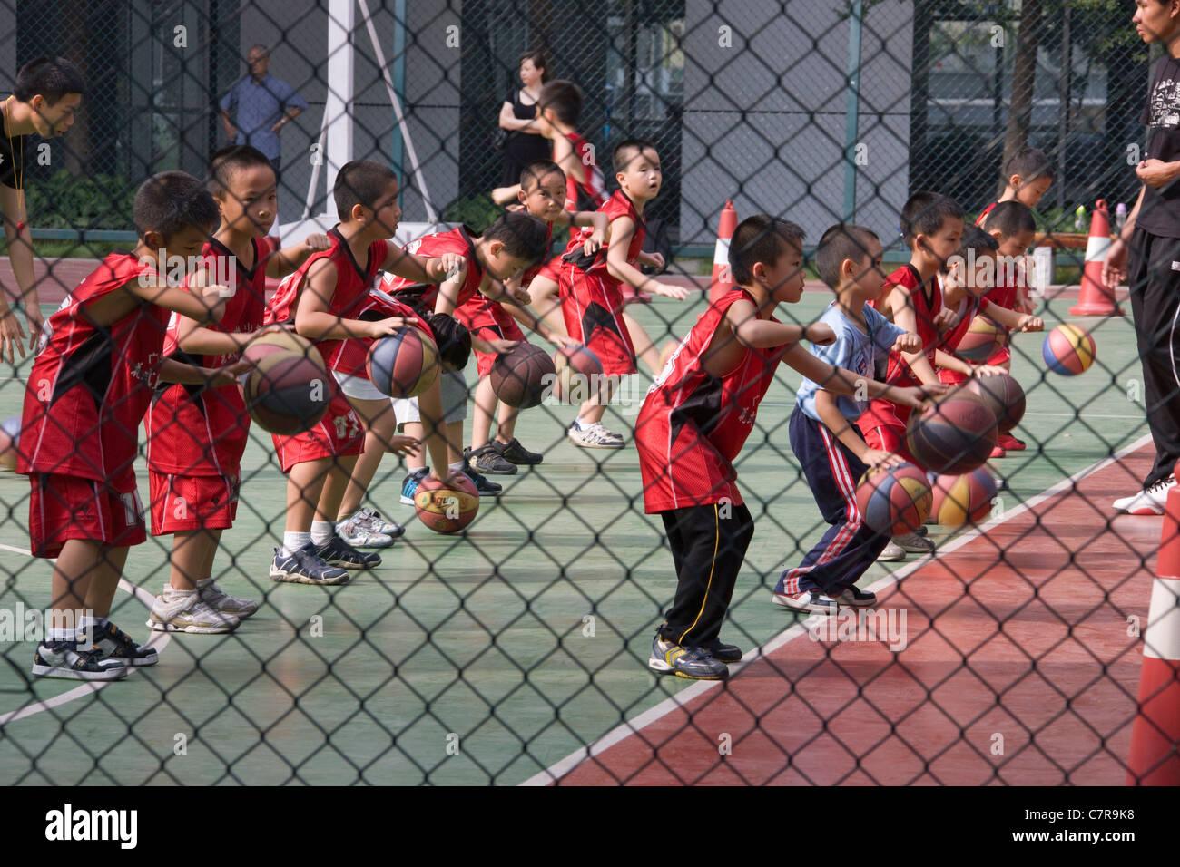 Children playing basketball at school, Guangzhou, Guangdong, China - Stock Image