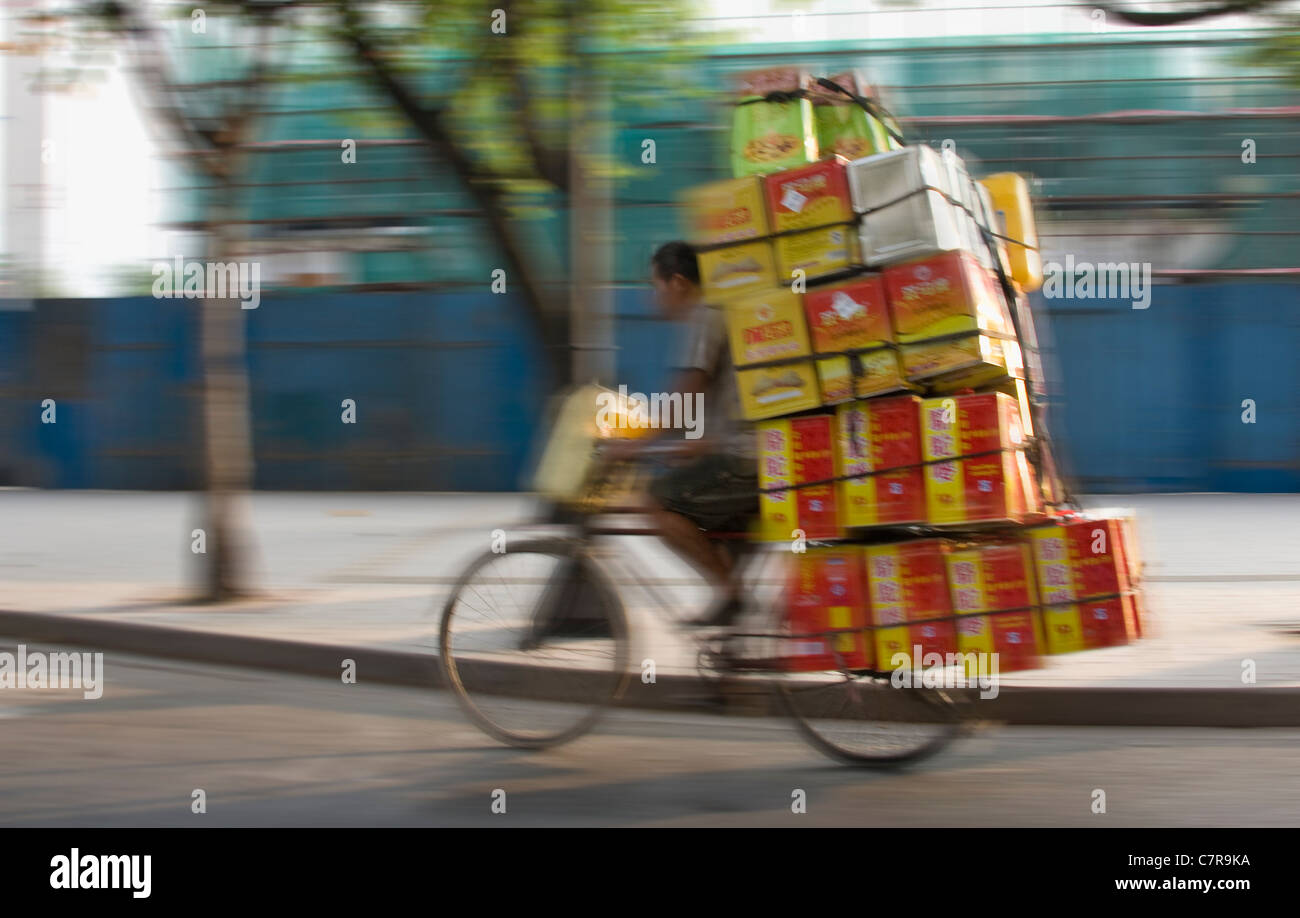 Man riding bicycle with a large load on the street, Guangzhou, Guangdong, China - Stock Image
