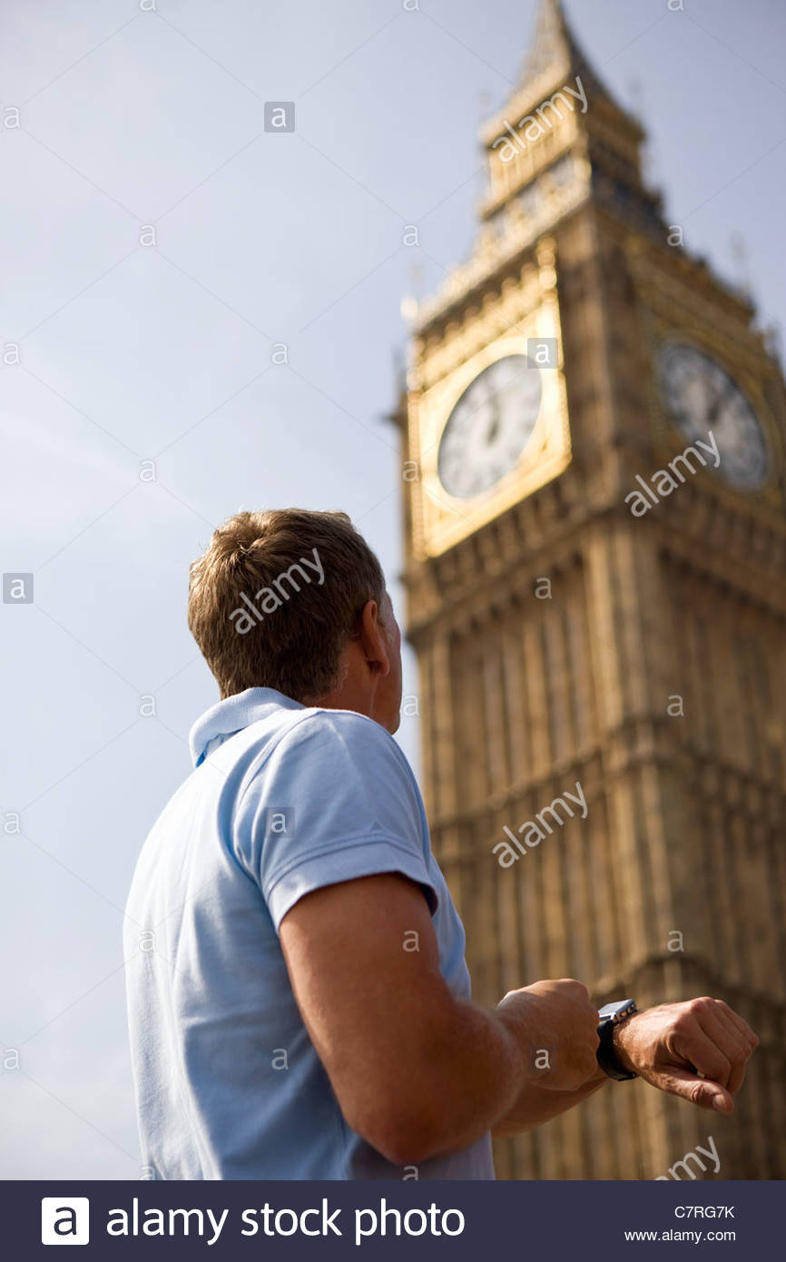 A middle-aged man checking his watch next to Big Ben - Stock Image