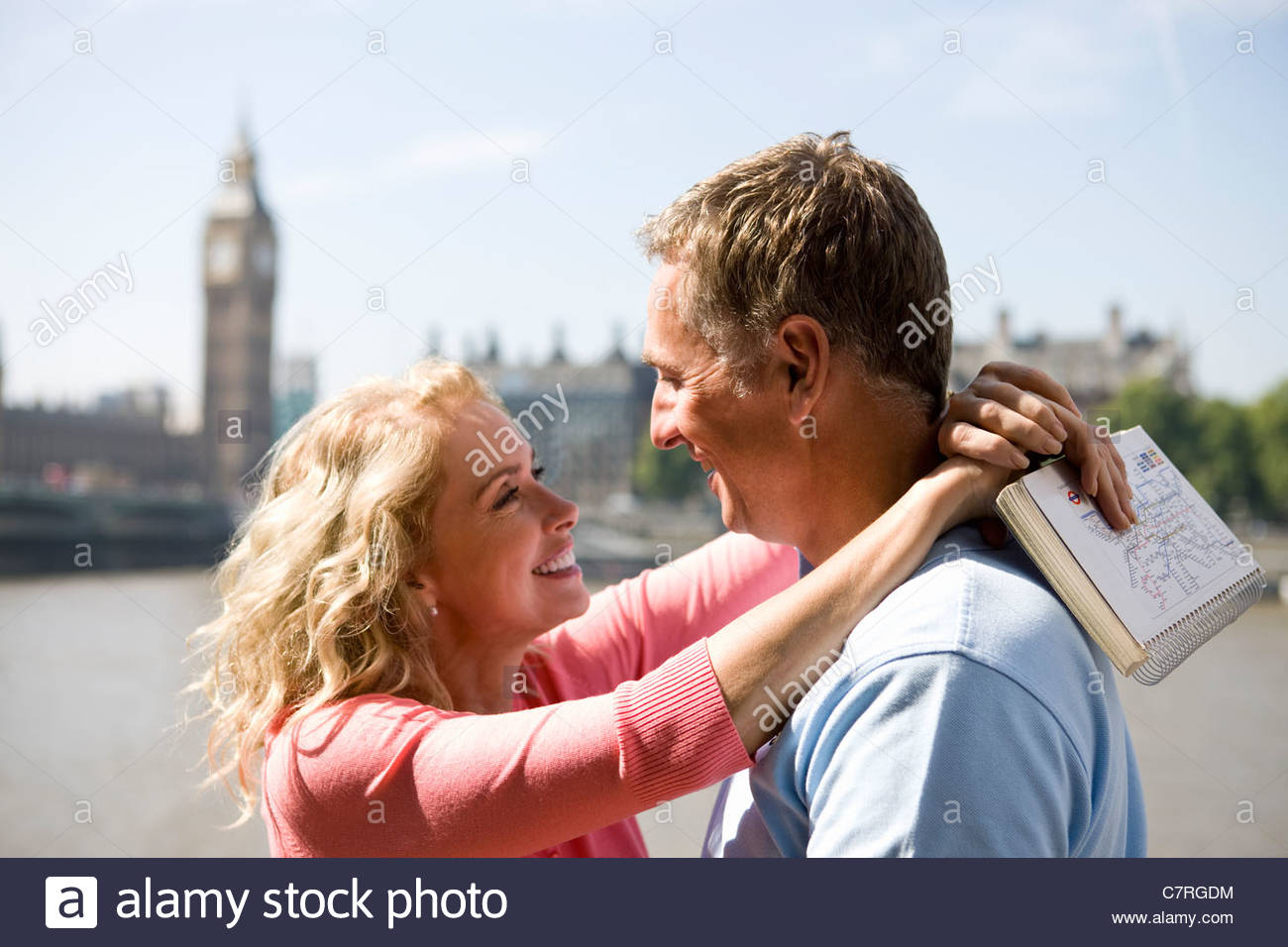 A middle-aged couple standing near the Houses of Parliament, embracing - Stock Image