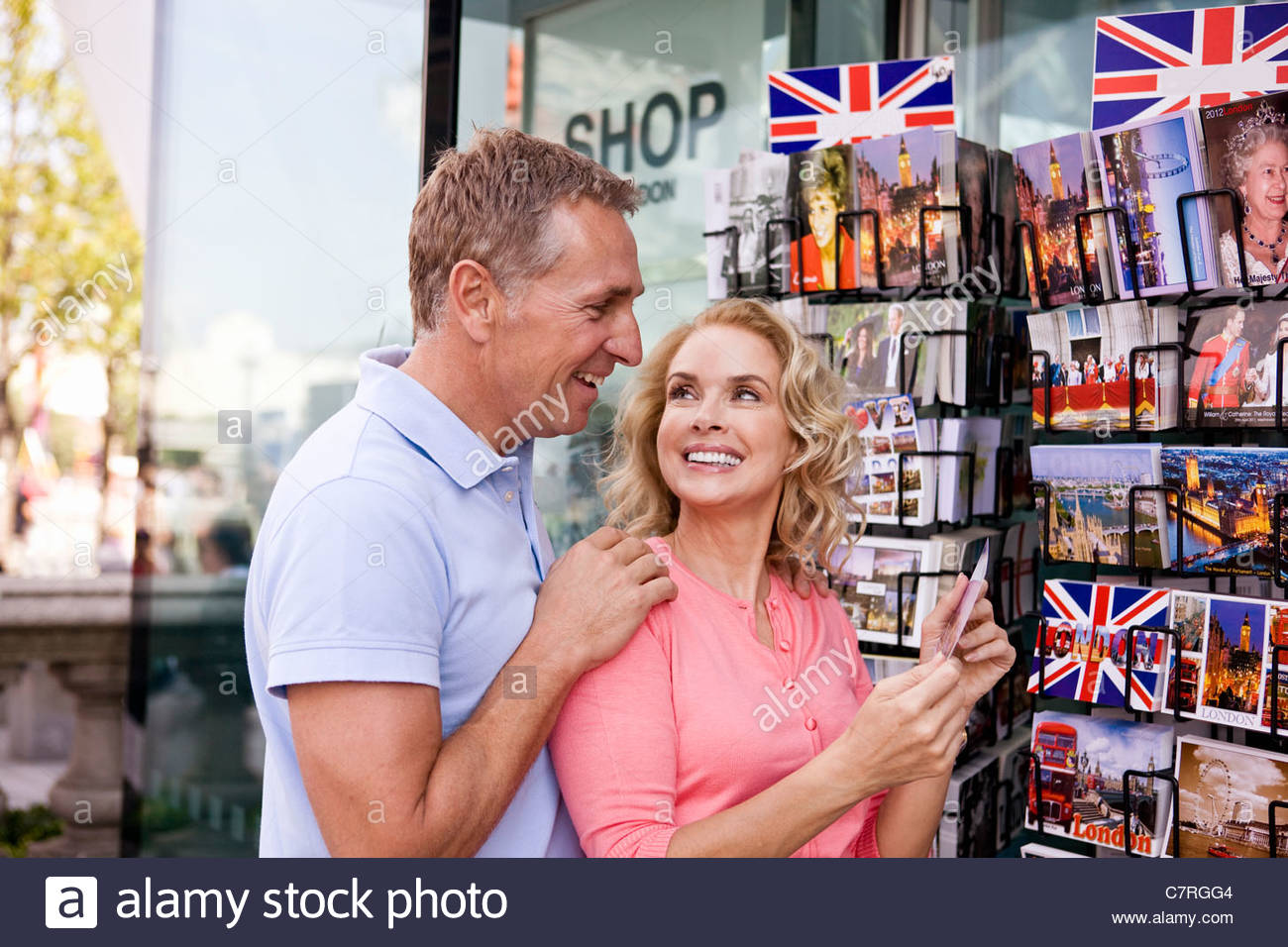 A middle-aged couple looking at postcards outside a souvenir shop - Stock Image