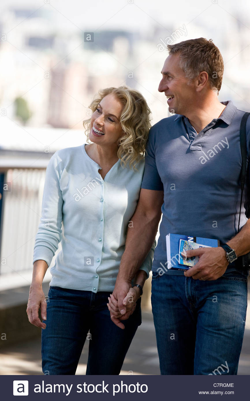 A middle-aged couple walking hand in hand, next to the river Thames - Stock Image