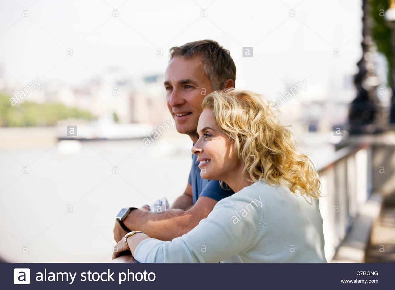 A middle-aged couple standing next to the river Thames, admiring the view - Stock Image