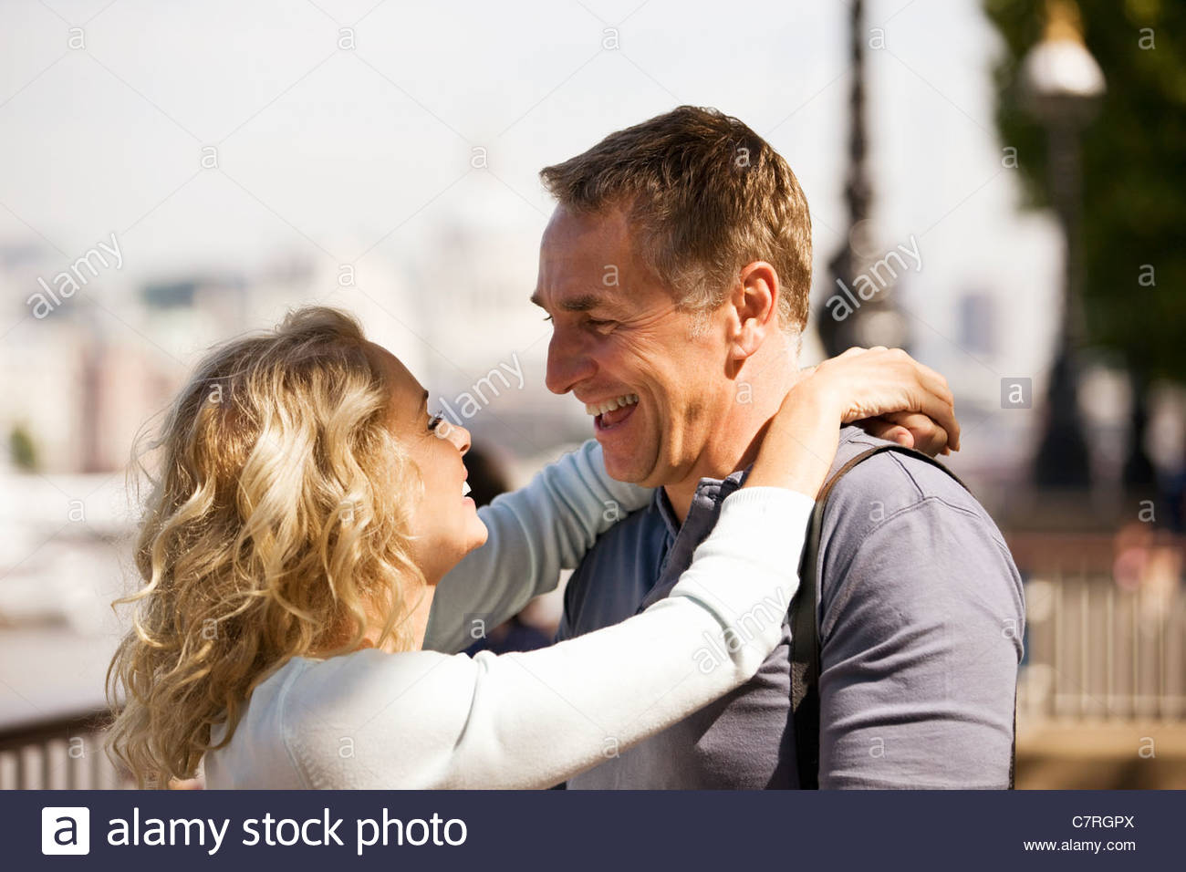 Portrait of a middle-aged couple next to the river Thames embracing - Stock Image