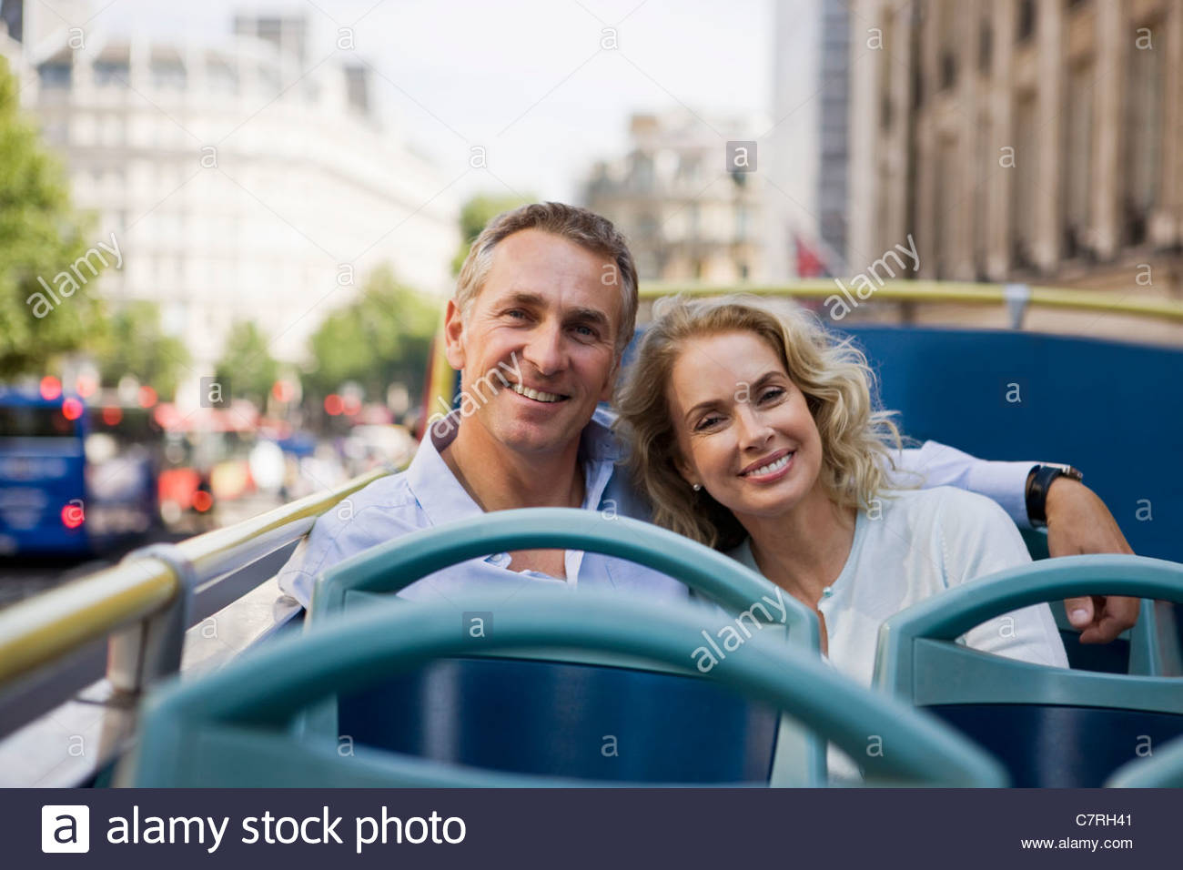 A middle-aged couple sitting on a sightseeing bus, embracing - Stock Image