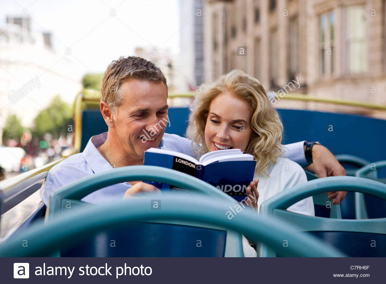 A middle-aged couple sitting on a sightseeing bus, looking at a guidebook - Stock Image