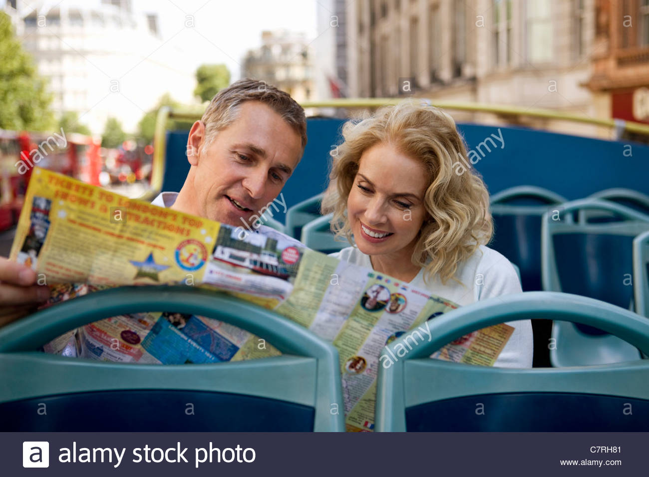 A middle-aged couple sitting on a sightseeing bus, looking at a map - Stock Image