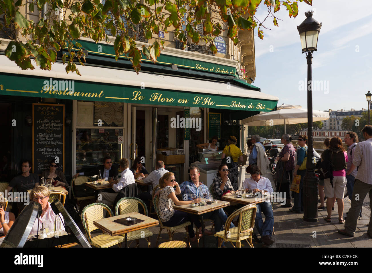 A restaurant on the Ile St Louis, Paris, with a queue to the right for Berthillon ice cream, Paris, France - Stock Image
