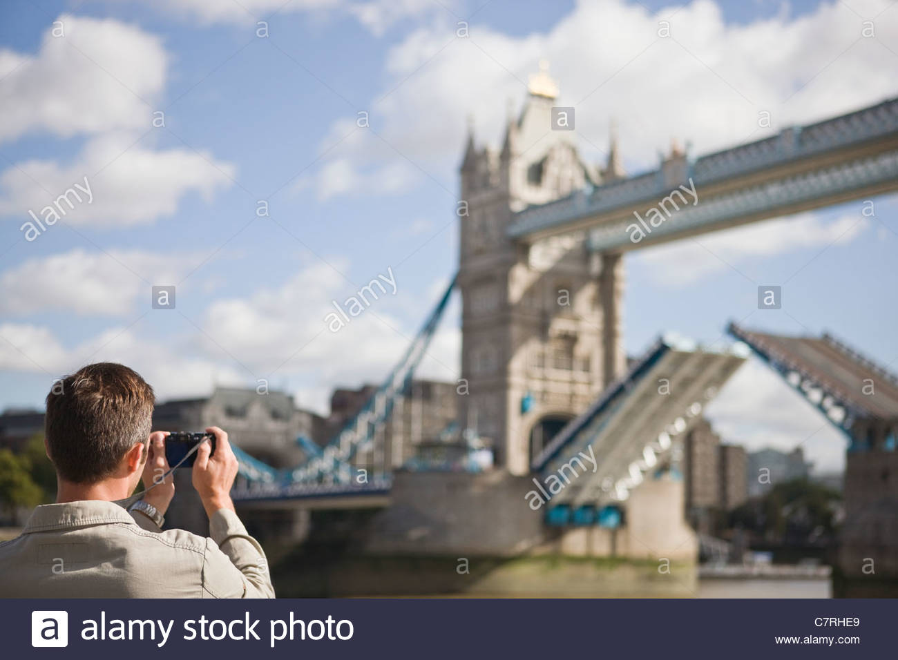 A mid-adult man taking a photograph of Tower Bridge - Stock Image