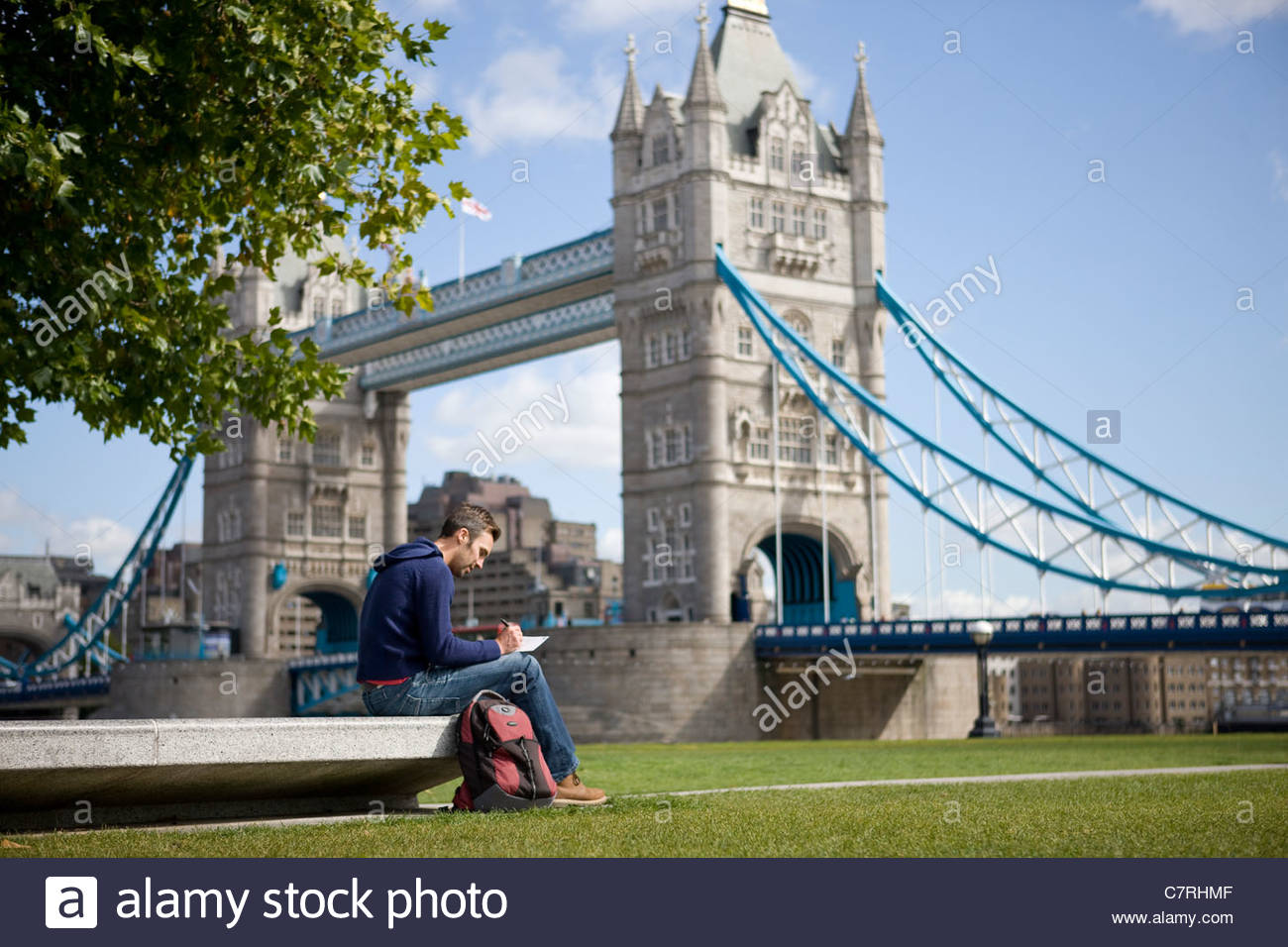 A mid-adult man sitting near Tower Bridge, writing a postcard - Stock Image