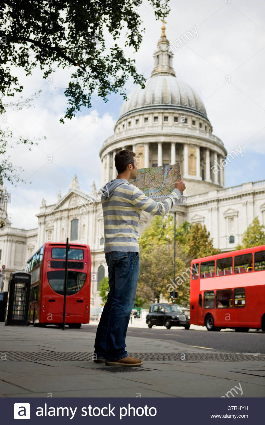 A mid-adult man standing in front of St Paul's cathedral, looking at a map - Stock Image