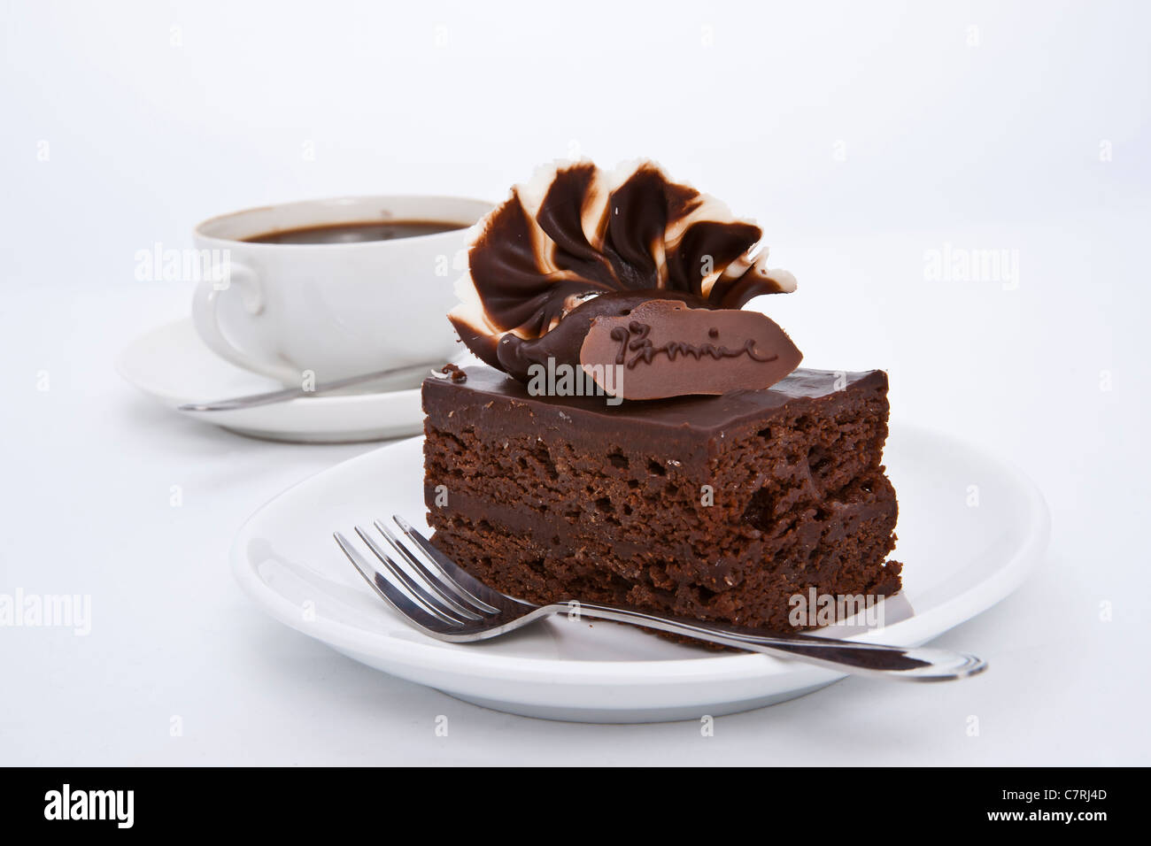 Delicious brownie cake with luxury cream topping and coffee - Stock Image