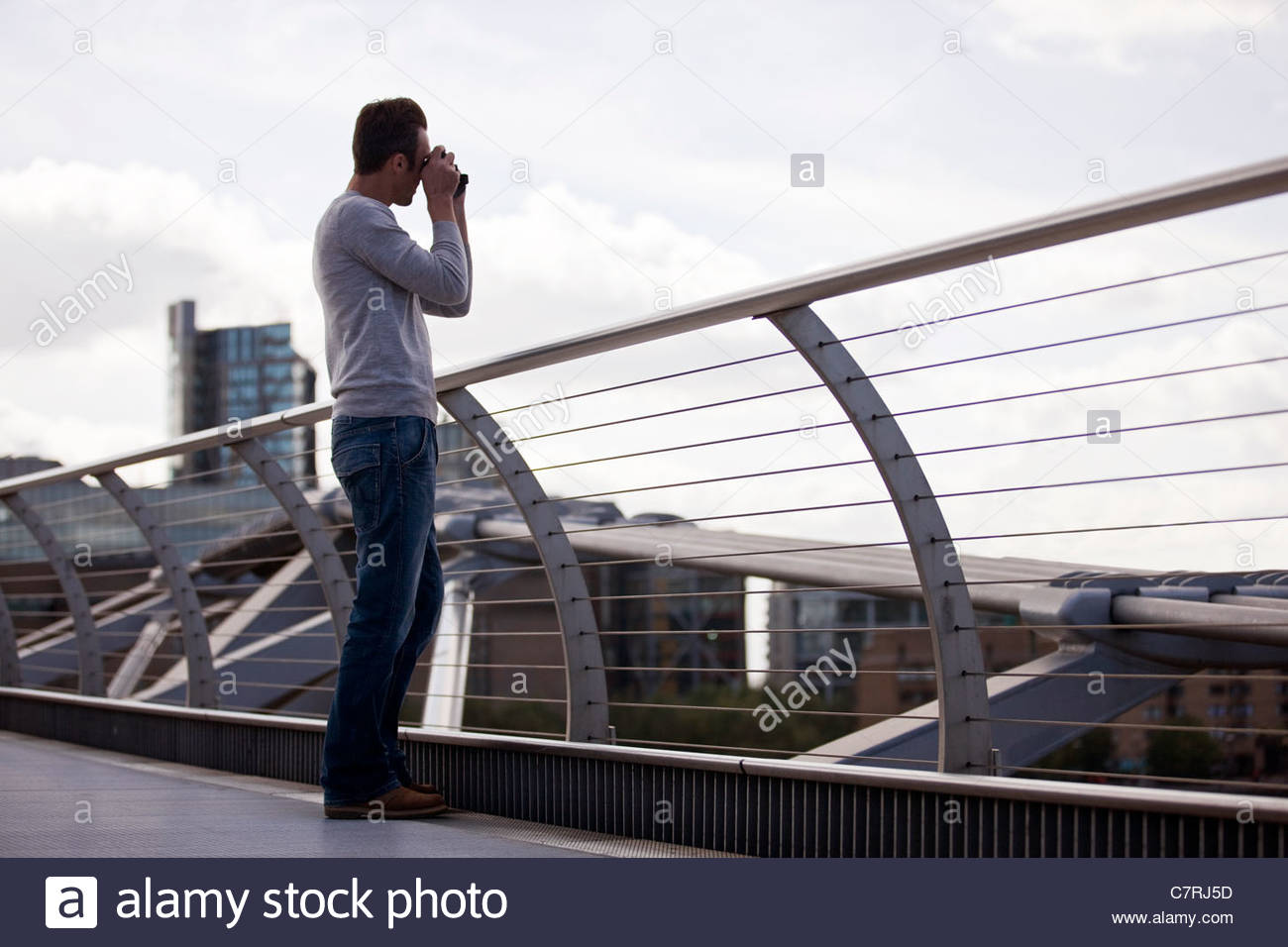 A mid-adult man standing on the Millennium Bridge, taking a photograph - Stock Image