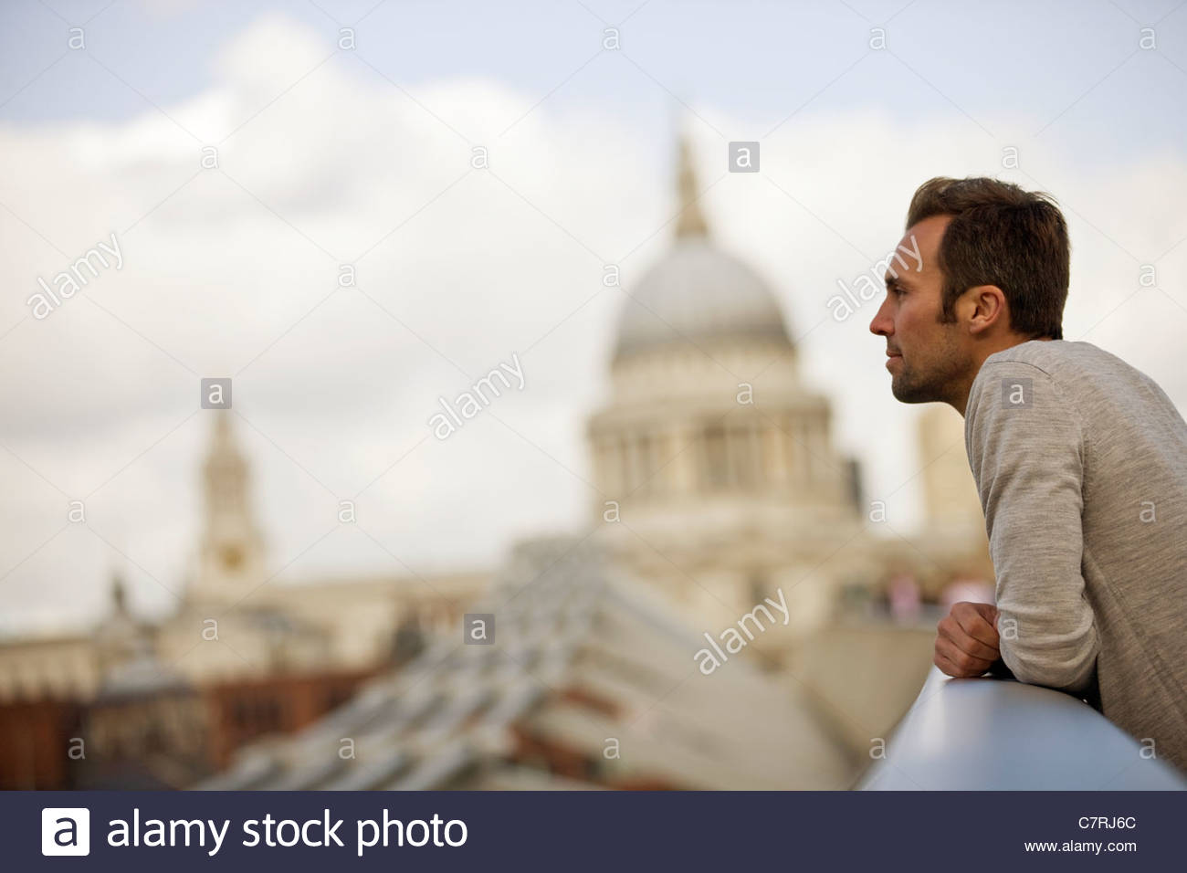 A mid-adult man standing on the Millennium Bridge, admiring the view - Stock Image