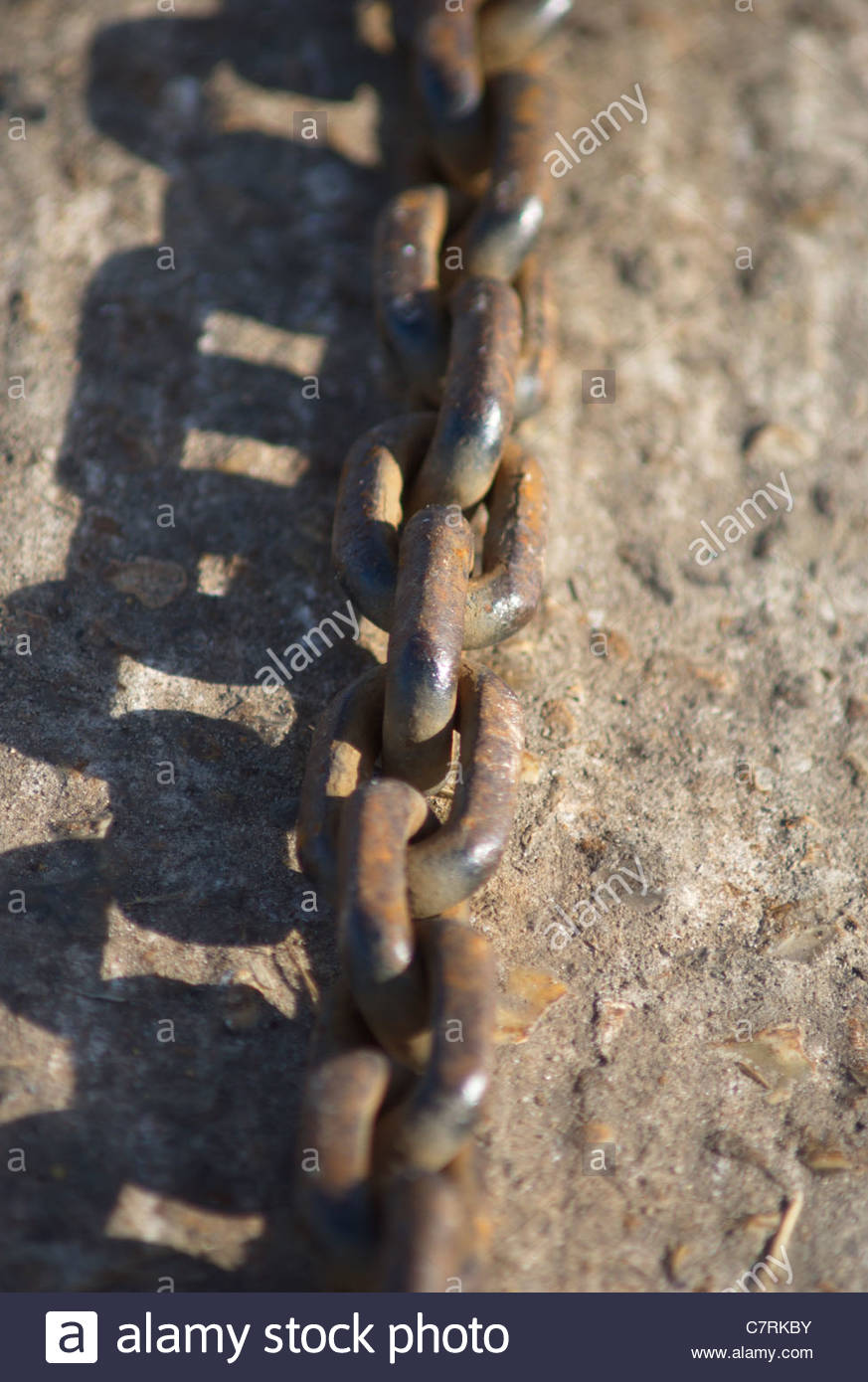 rusty chain on harbour wall - Stock Image