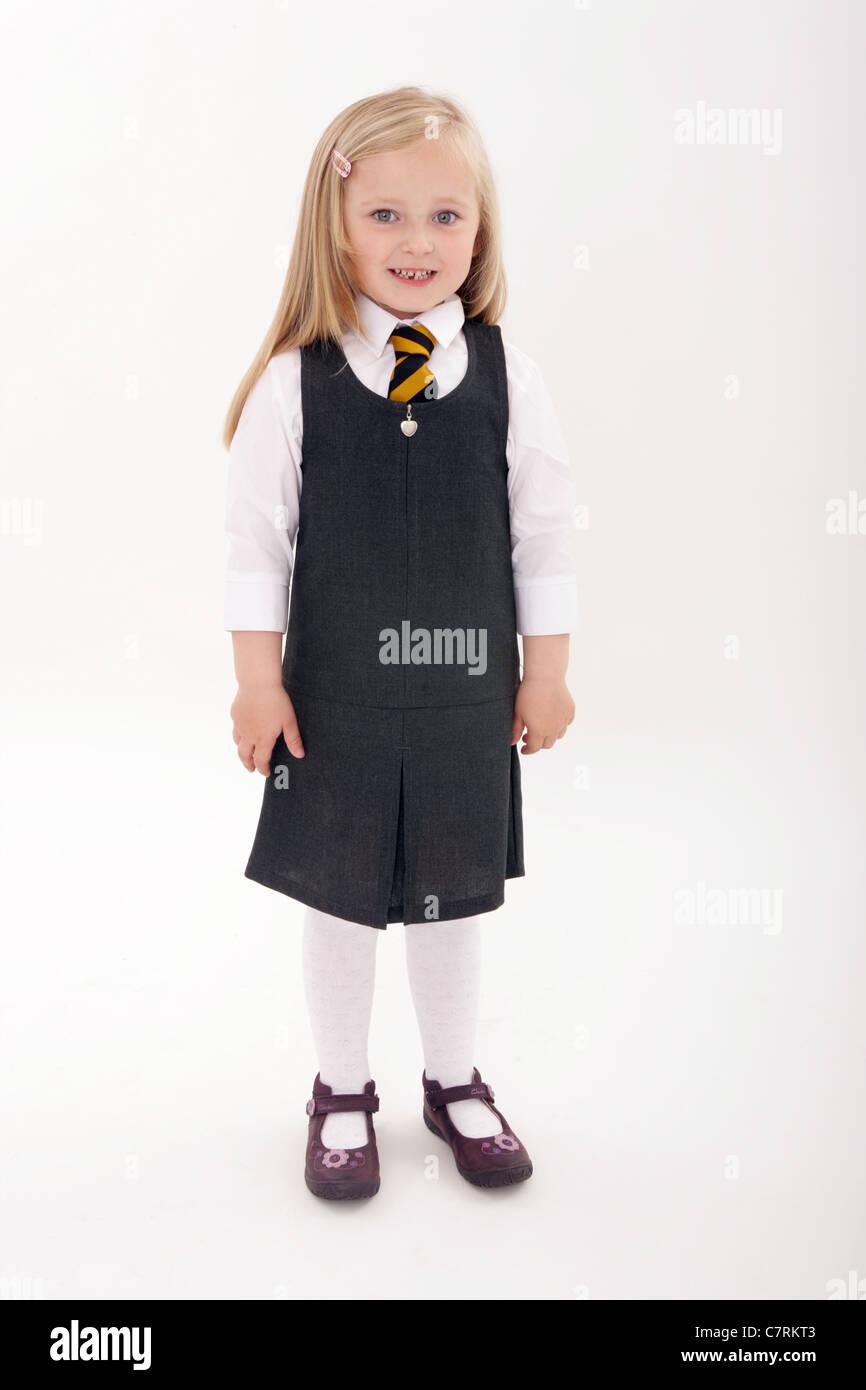Five year old girl standing in her new school uniform Stock