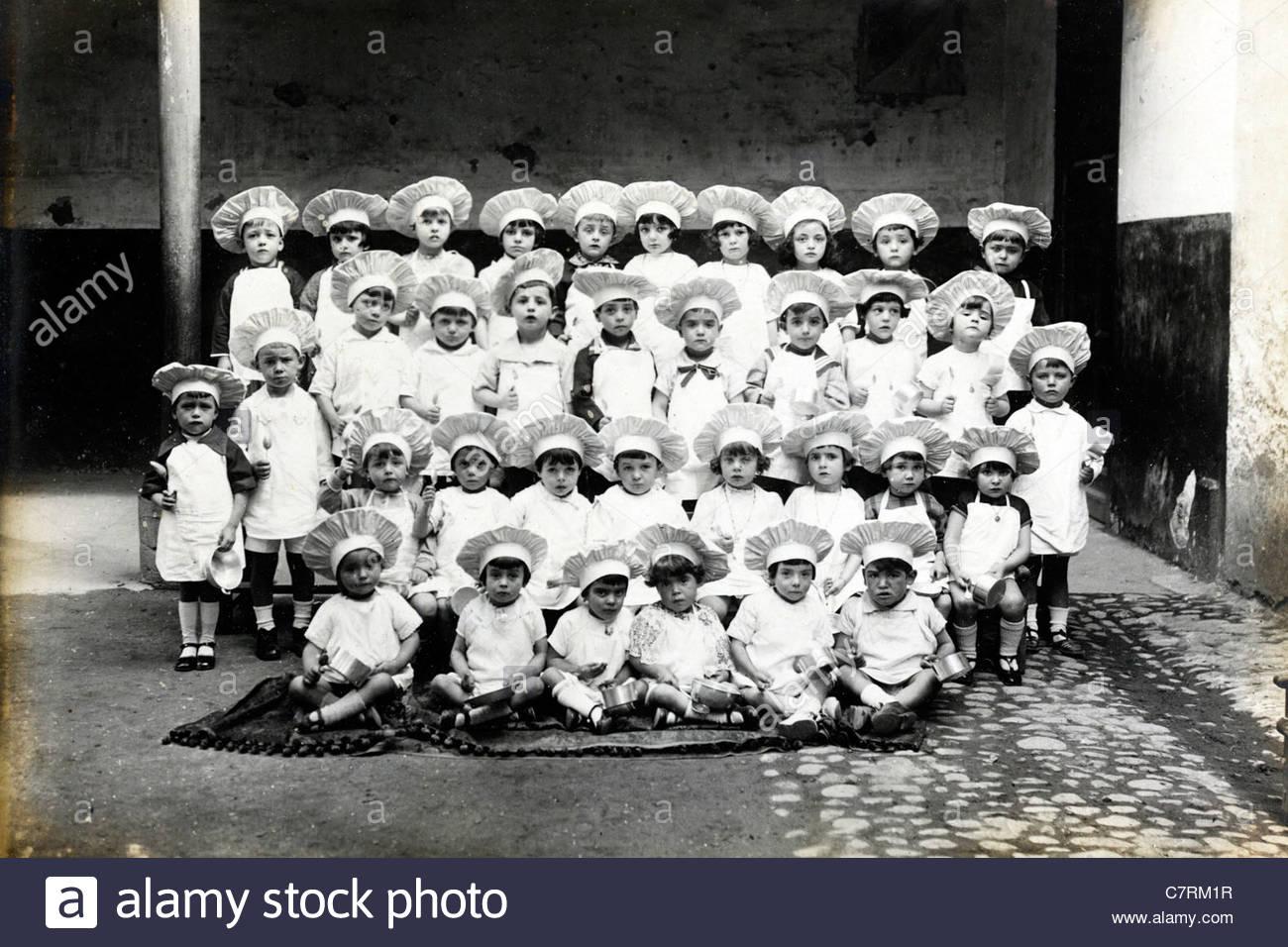 vintage formal group photo of little children dressed up as cook France - Stock Image