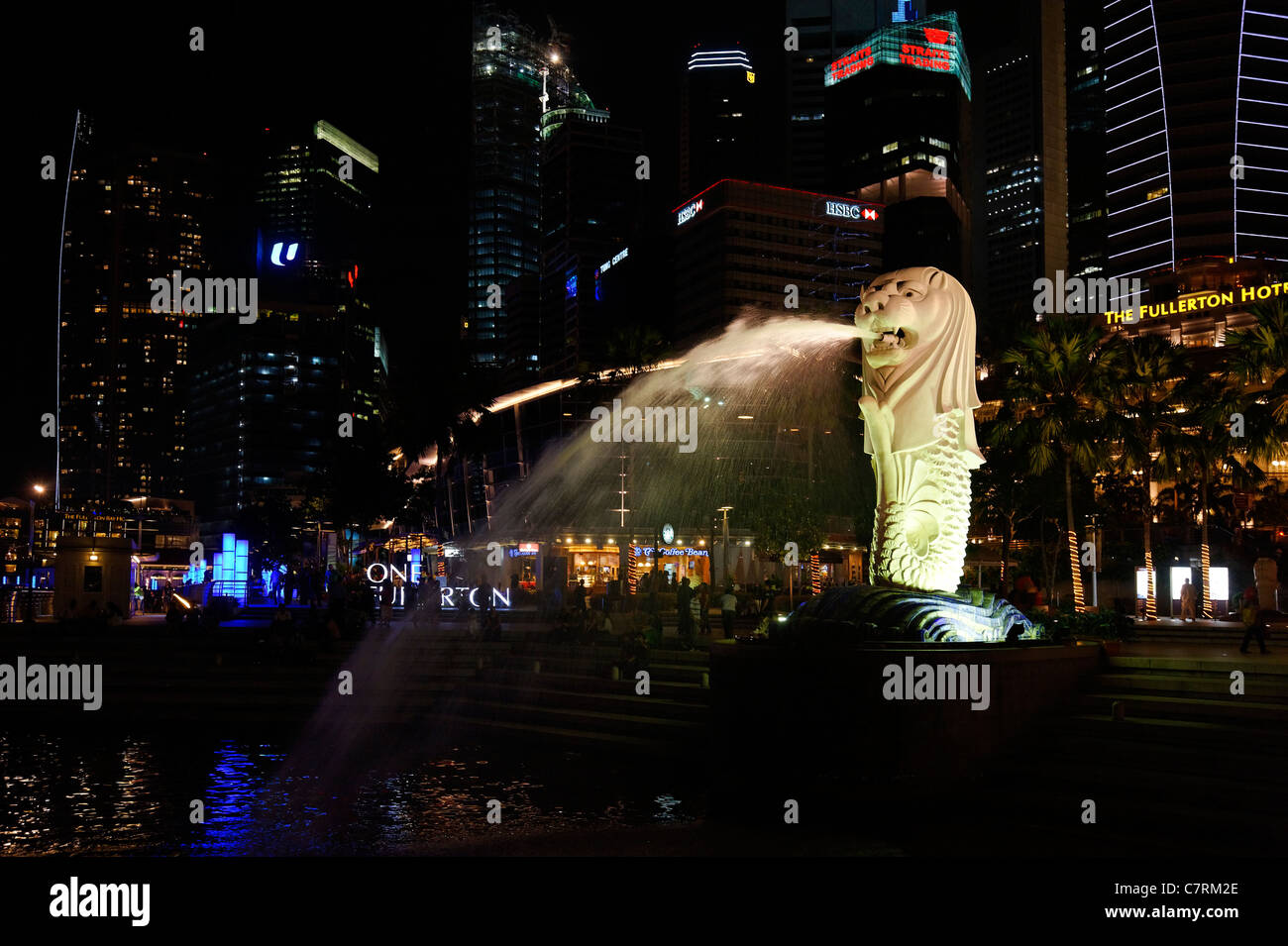 Floodlit Singapore Merlion fountaining spouting water at night with the business district and Fullerton Hotel behind. - Stock Image