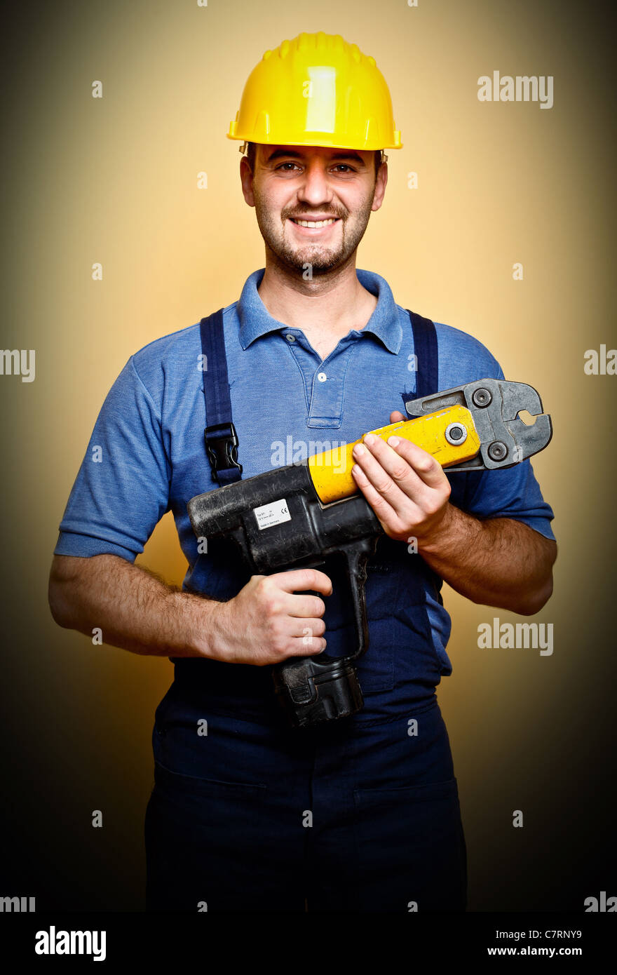 portrait of standing manual worker holding electric tool - Stock Image