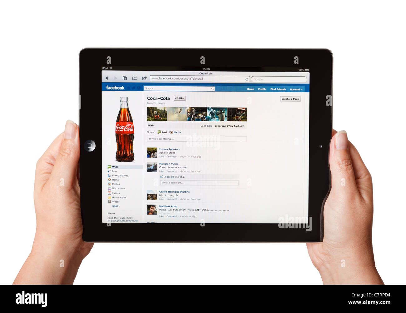 Female hands holding iPad showing online Coca Cola Facebook page - Stock Image