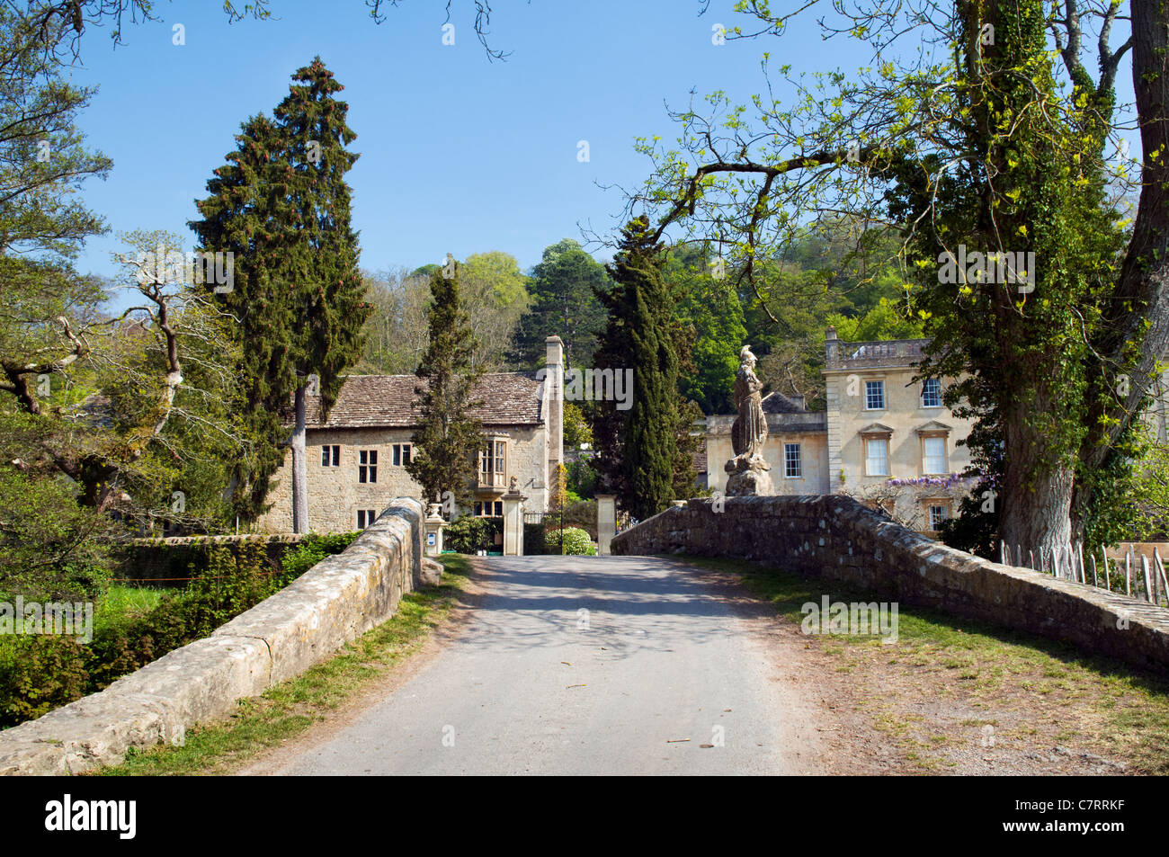 Picturesque scene at Iford of single track road, bridge and Iford manor, taken at Iford, Bradford on avon on fine - Stock Image