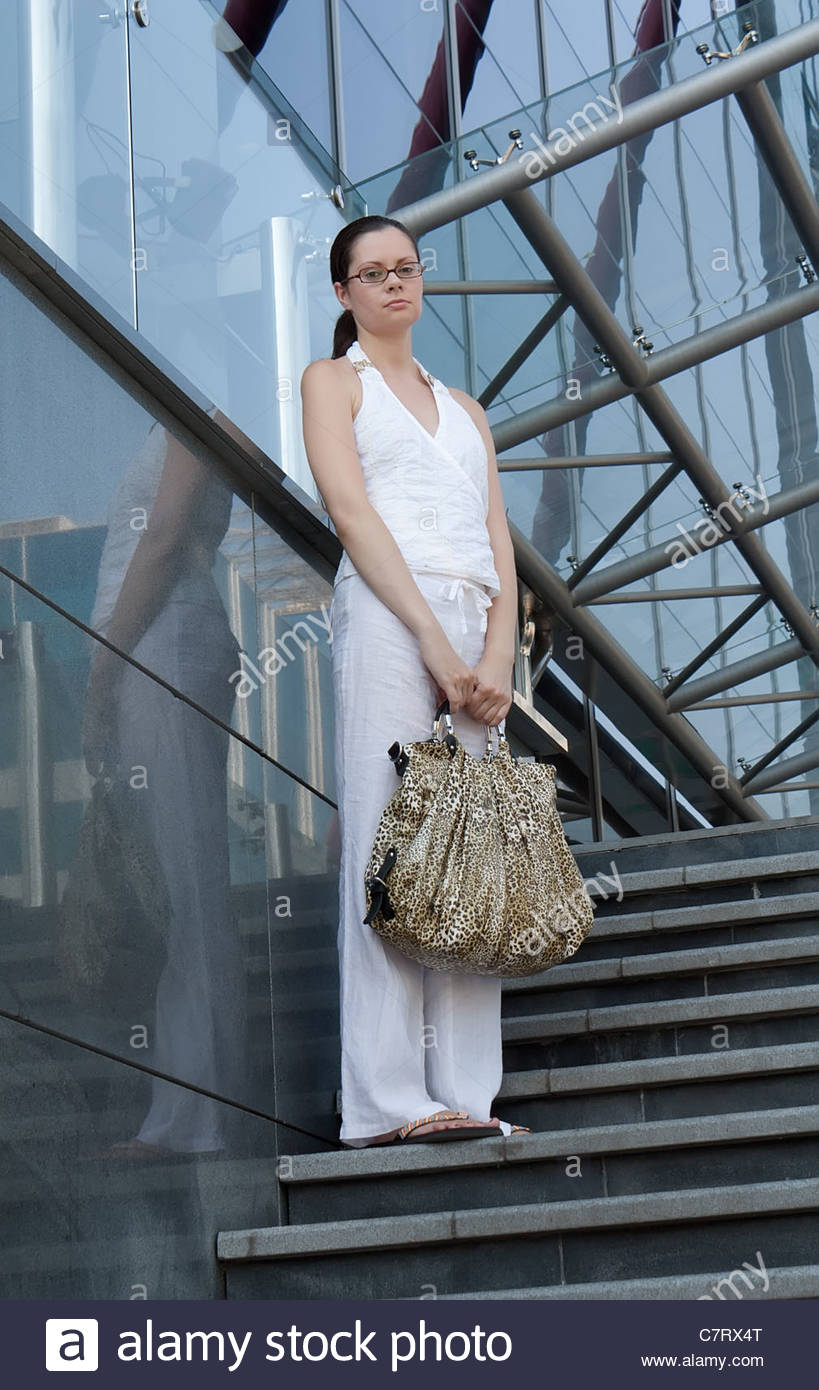 Young woman with leopard bag stand on stair  near modern building - Stock Image