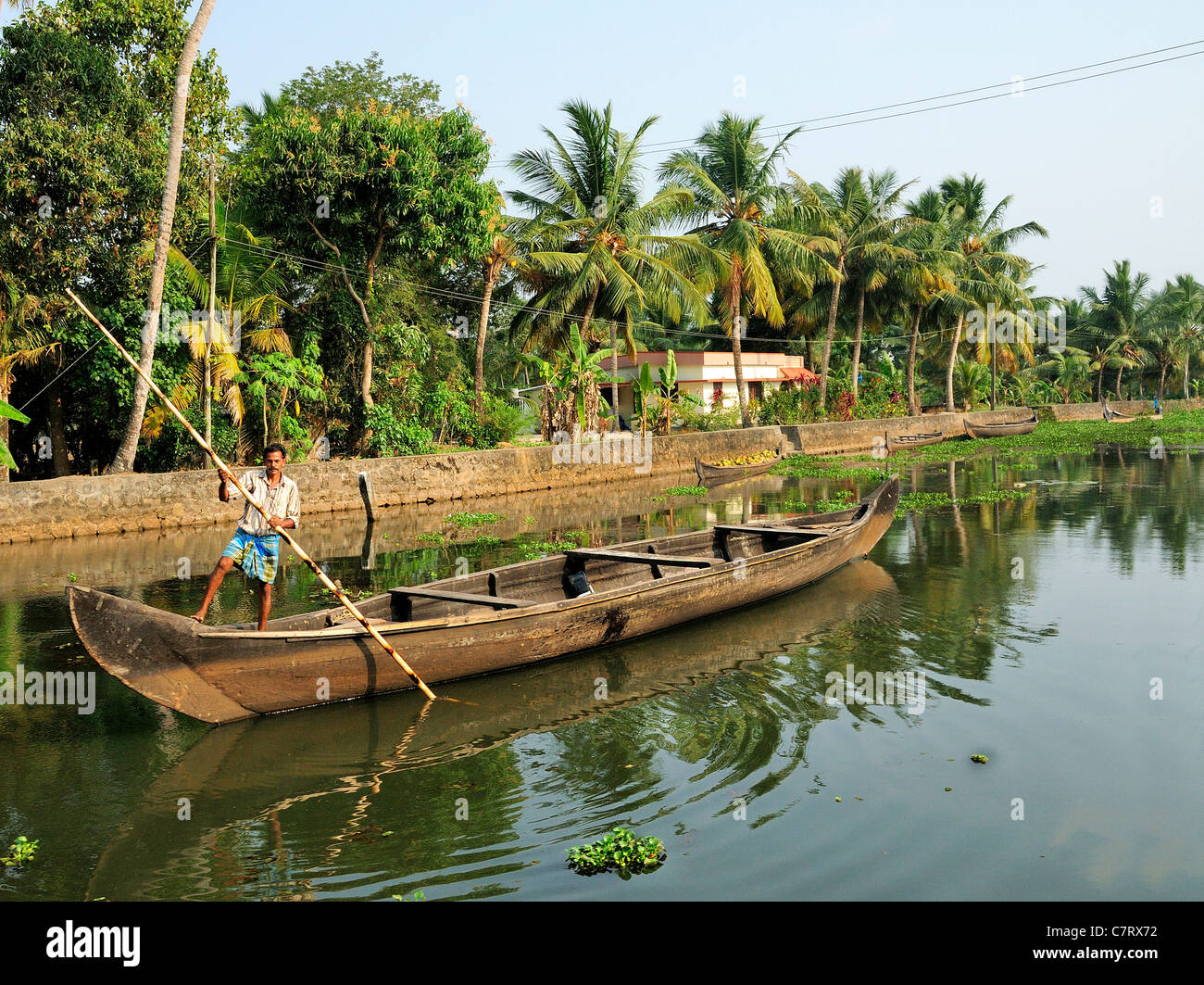 Man punting his empty work canoe along the back waters of Kerala India - Stock Image