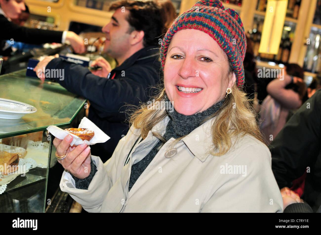 "Portugal, Lisbon: Lady from Brazil trying  the famous ""Pasteis de Belém"" in the Antiga Confeitaria de Belém Stock Photo"