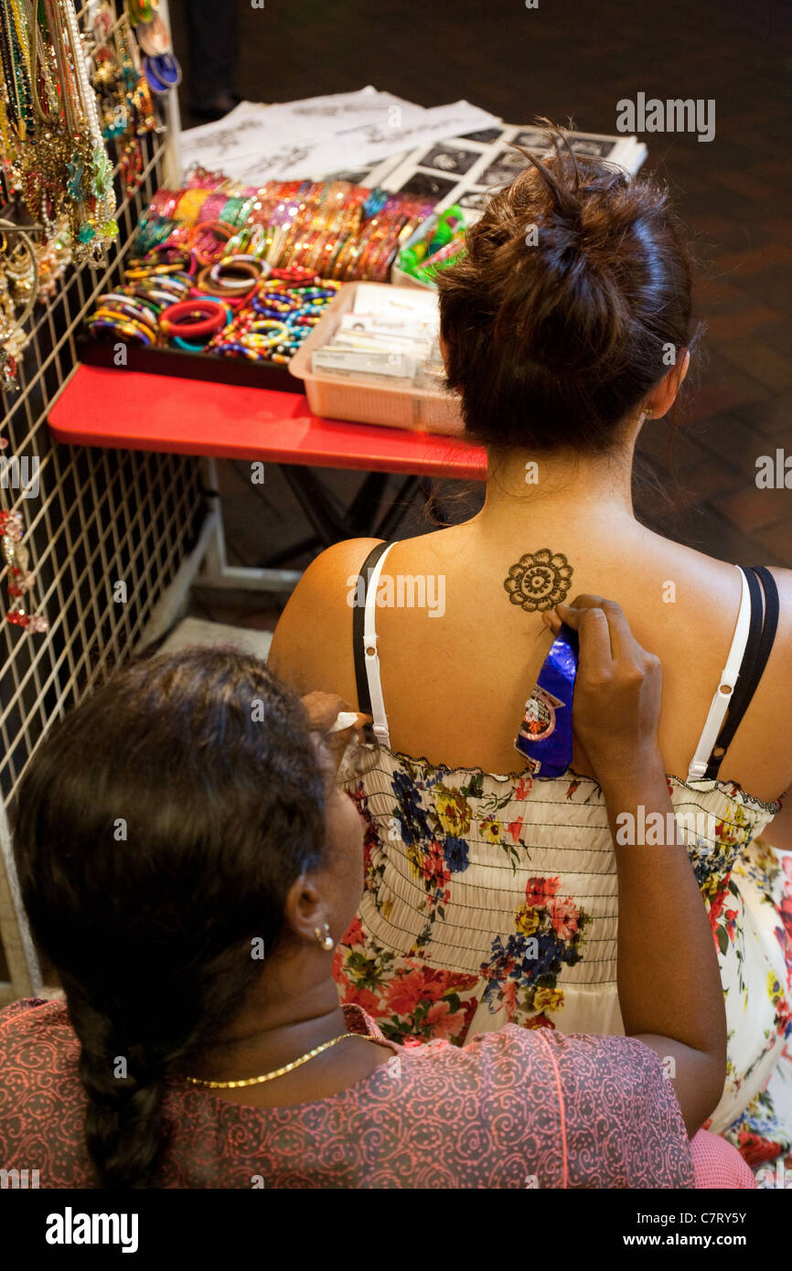A teenage girl gets a flower shaped henna tattoo, Chinatown, Singapore Asia - Stock Image