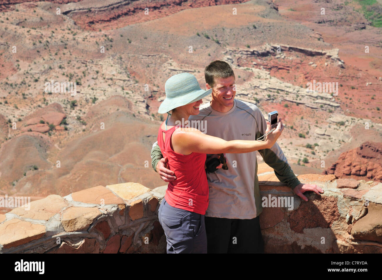 A couple photographs themselves at an overlook in Dead Horse Point State Park - Stock Image