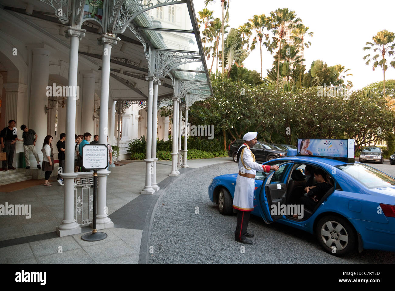 The Doorman opens the door to a taxi, Raffles Hotel, Singapore - Stock Image