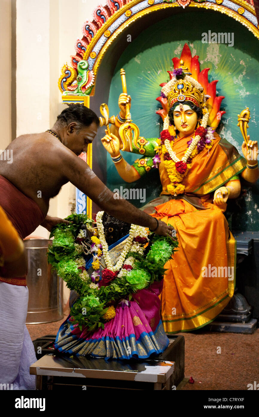 A Hindu priest makes an offering to the goddess Durga, a Hindu deity, The Sri mariamman Temple, Singapore Asia - Stock Image