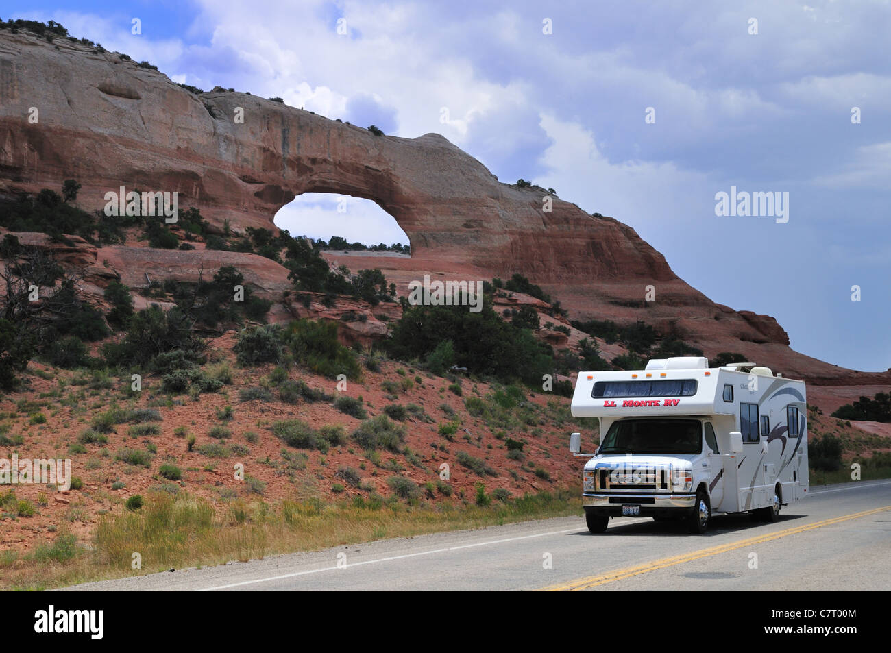 A motorhome camper glides by the Wilson arch, Monticello, Utah - Stock Image