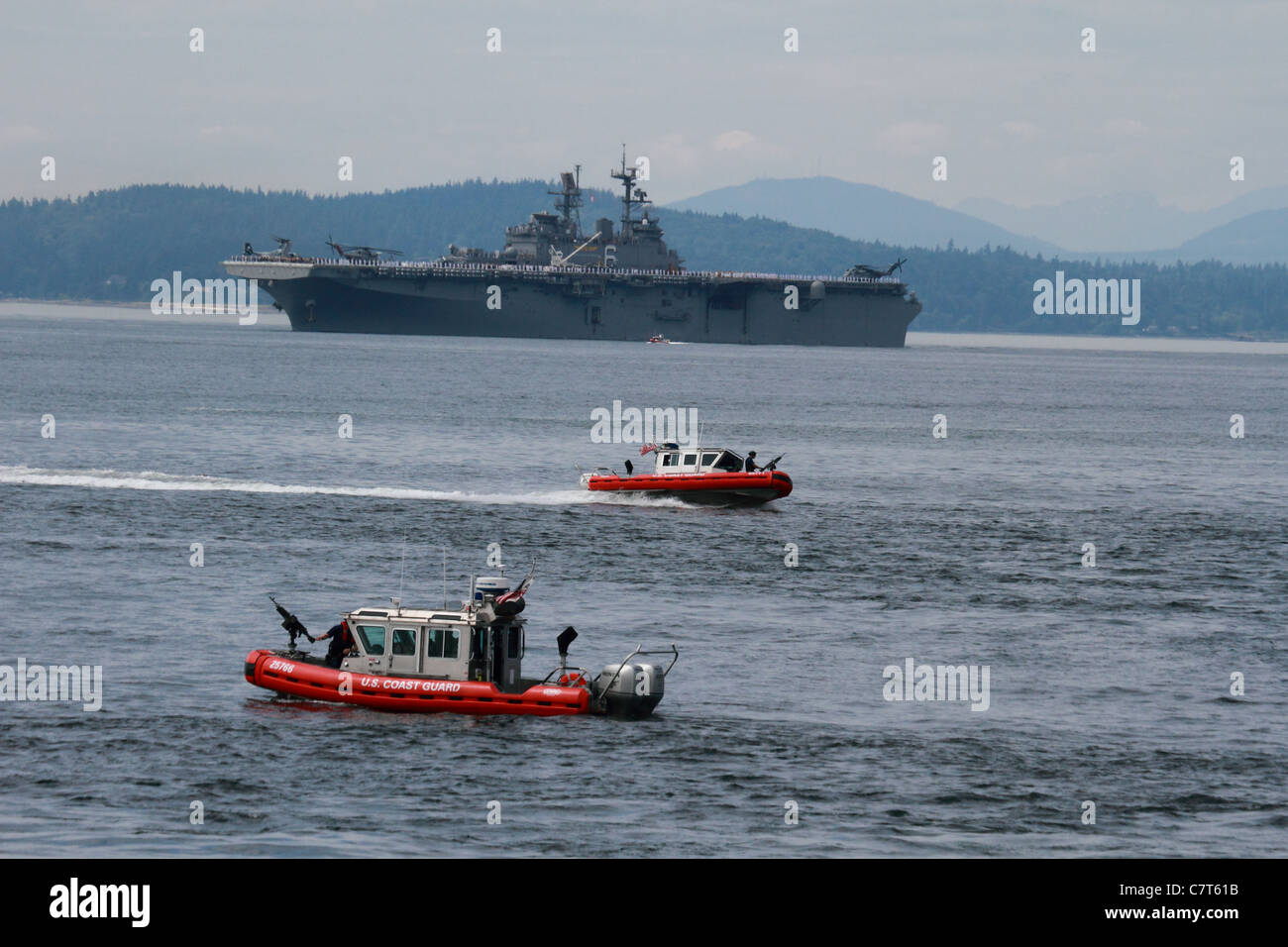 US Coast Guard patrol boats securing the way for the Amphibious Assault Ship the USS Bonhomme Richard LHD-6 to dock Stock Photo