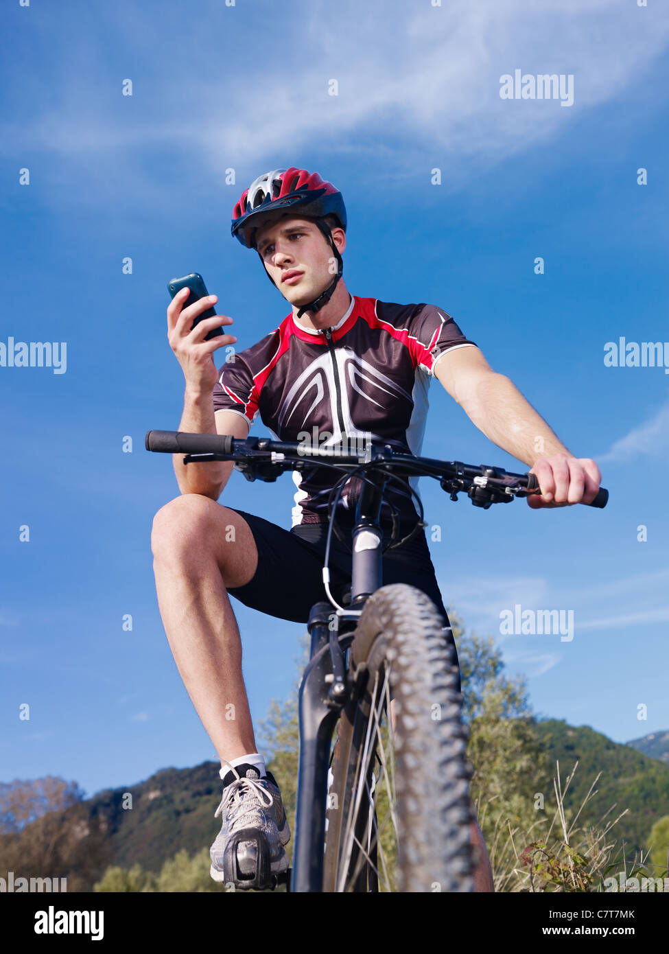 sports activity: young adult cyclist riding mountain bike and text messaging on cellphone. Vertical shape, low angle - Stock Image